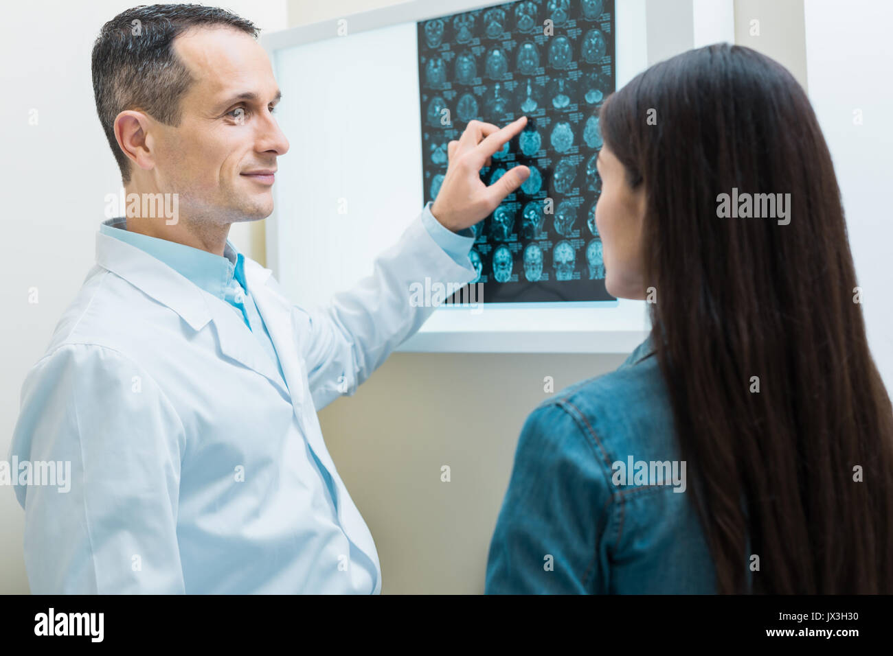 Pleasant doctor explaining the results of CT scan to patient - Stock Image