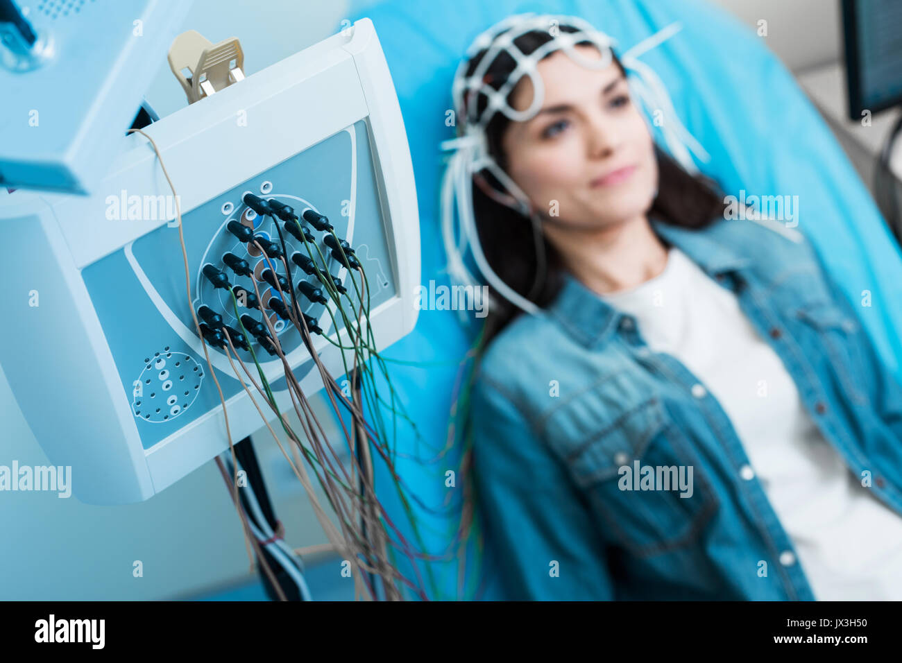 Close up of electroencephalograph recording brain waves of woman - Stock Image