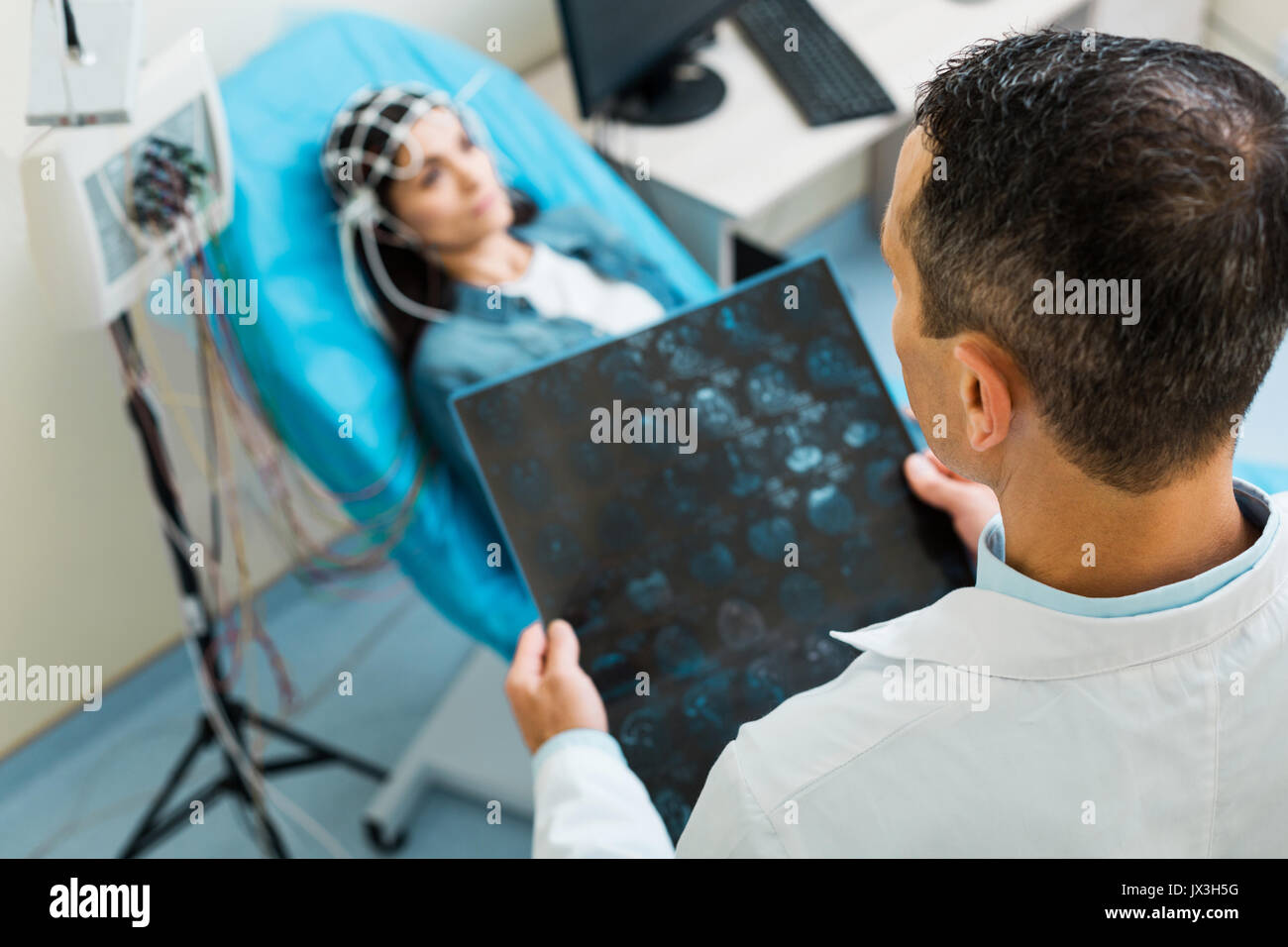 Top view of doctor scrutinizing CT results of young woman - Stock Image