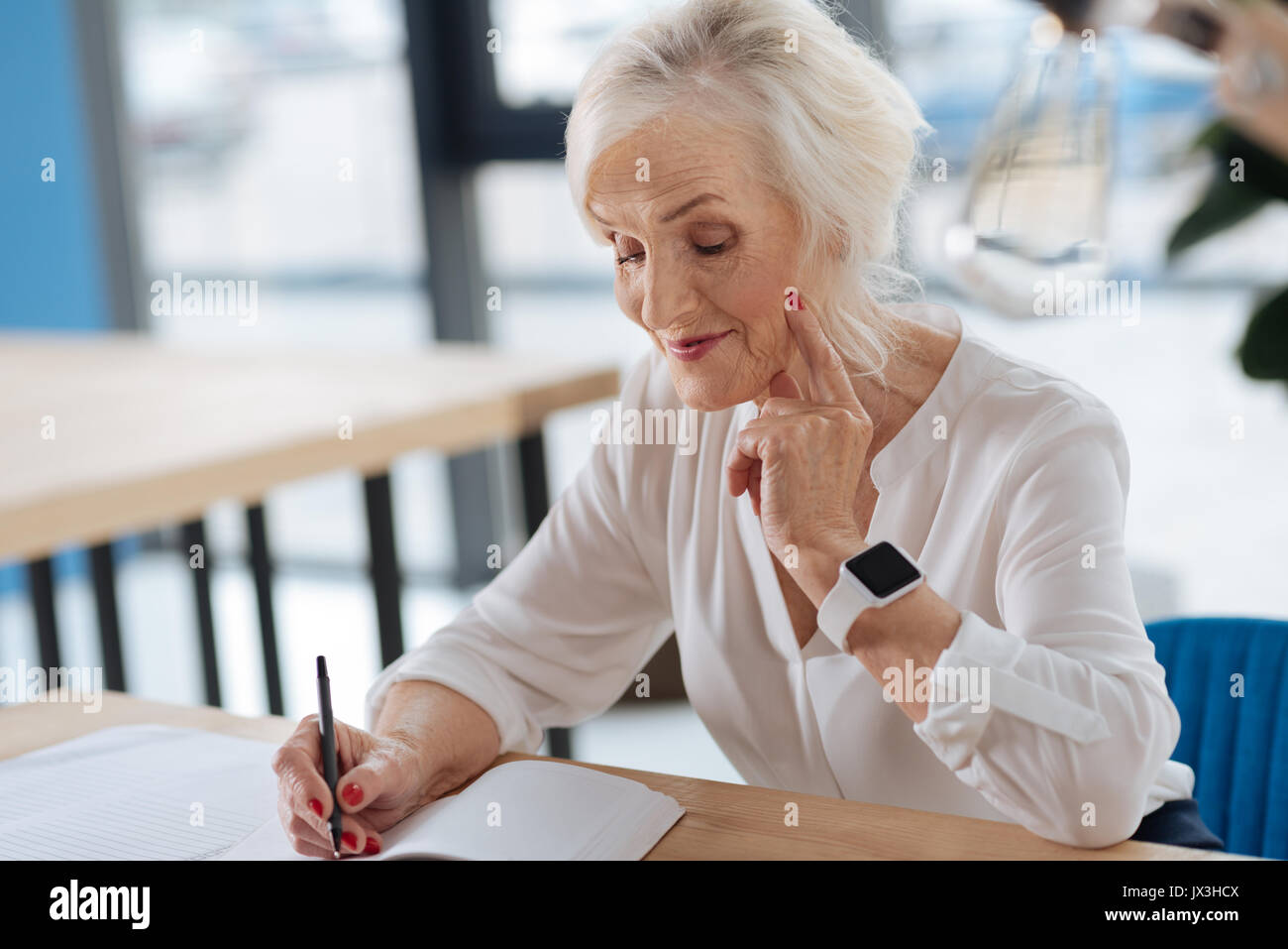 Happy aged woman writing down her memories - Stock Image