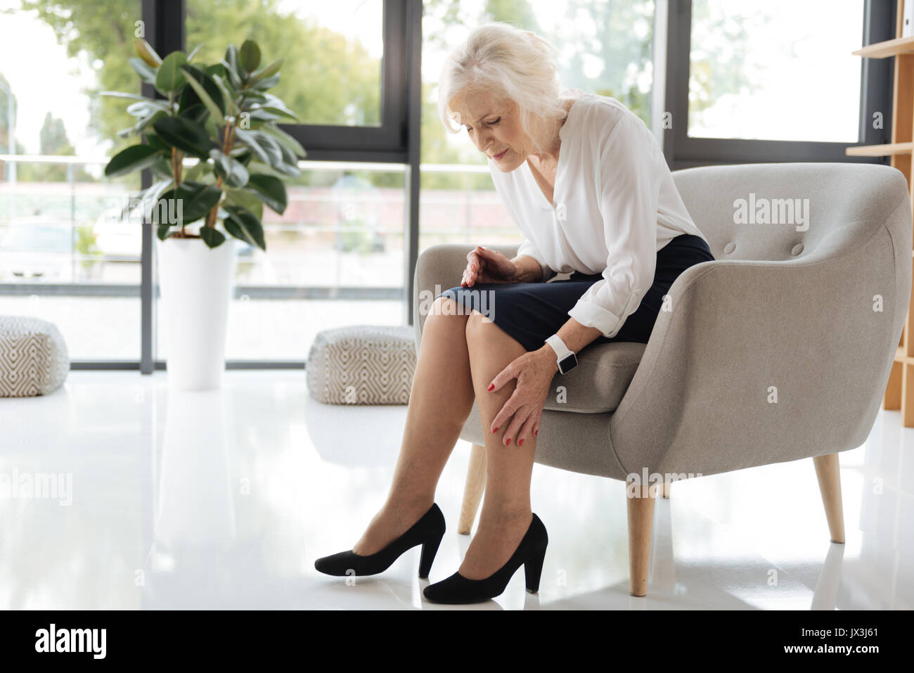 Unhappy cheerless woman looking at her legs - Stock Image
