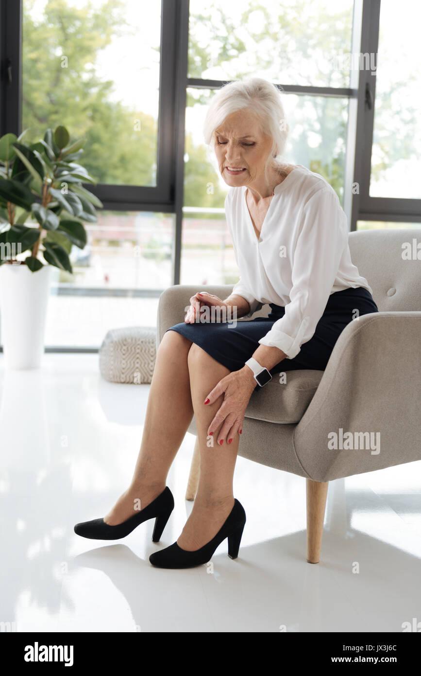 Gloomy senior woman feeling pain in her legs - Stock Image