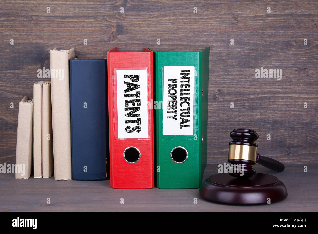 Patents and Intellectual Property. Wooden gavel and books in background. Law and justice concept. - Stock Image