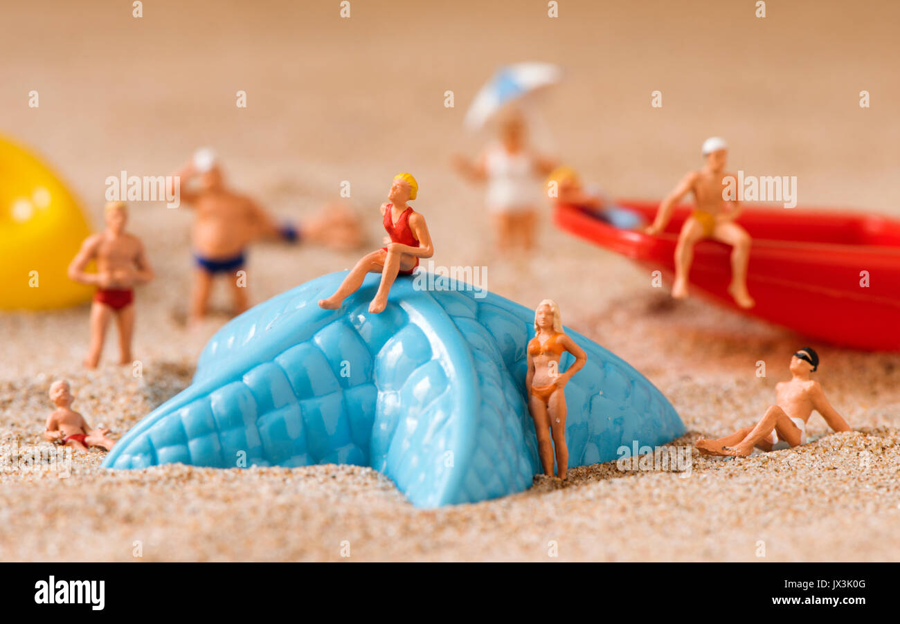 some different miniature people wearing swimsuit relaxing next to a blue plastic starfish and a red toy shovel on the sand of the beach - Stock Image