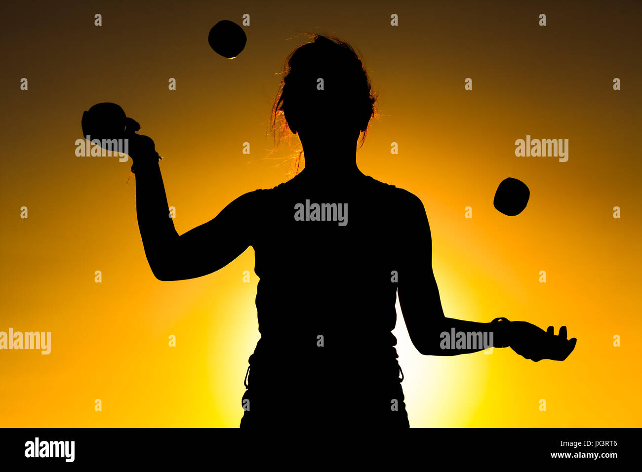 Silhouette of a Woman Juggling with Balls at Sunset - Stock Image