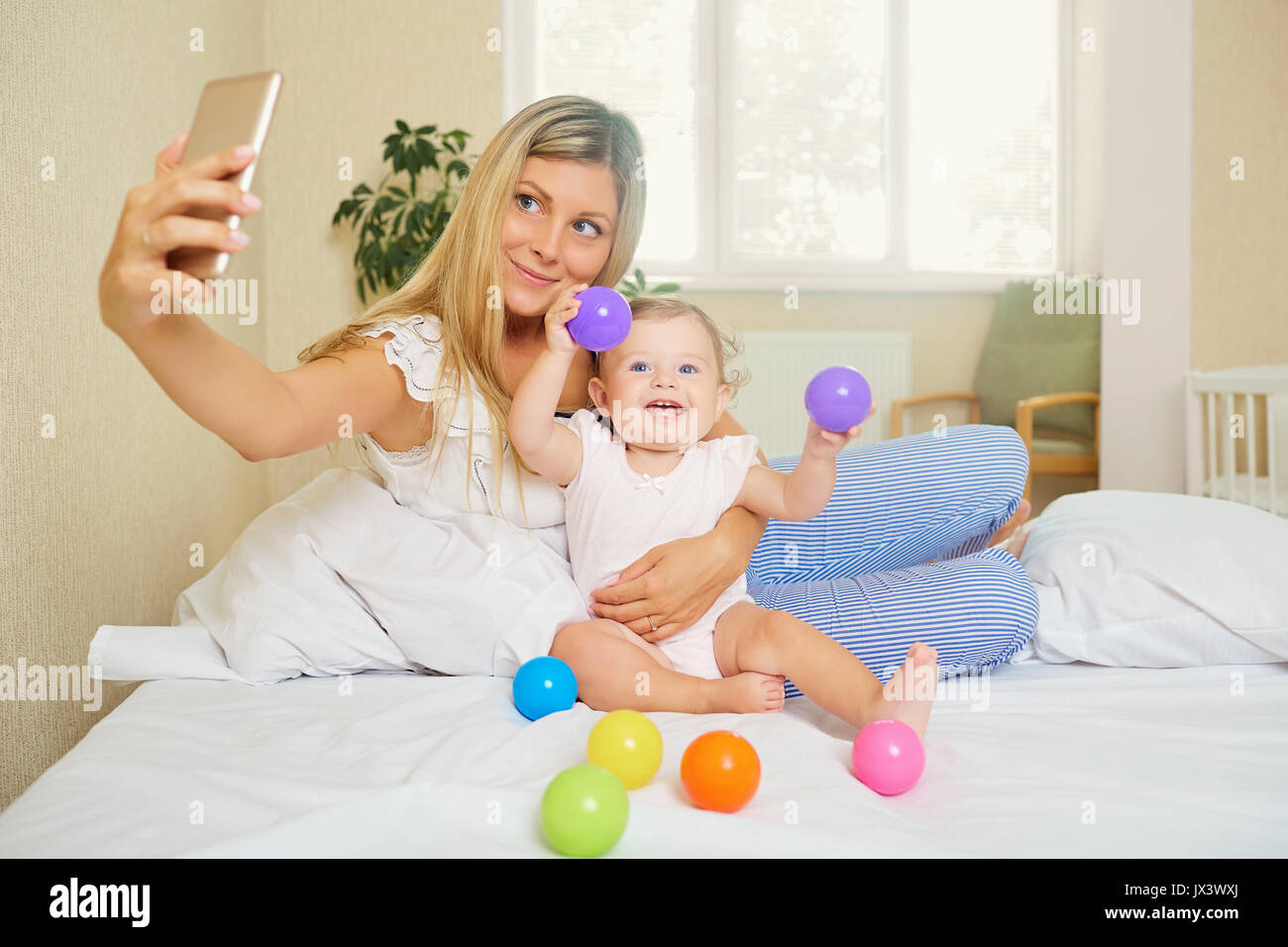 Mom makes a photo on the phone with the baby in the room. Salfie - Stock Image