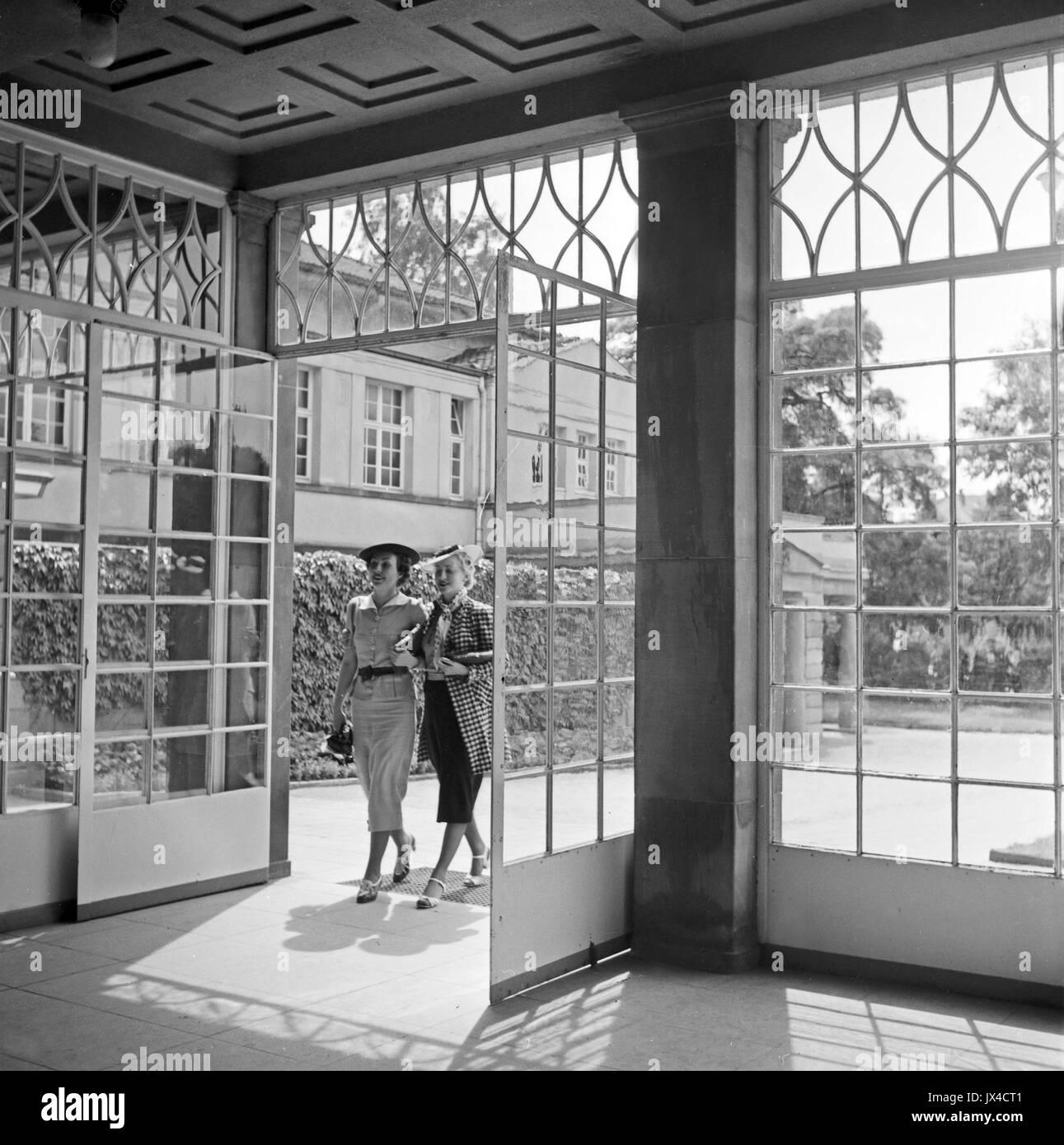 Two Well Dressed Women Walking Through Open Glass Door Into Resort