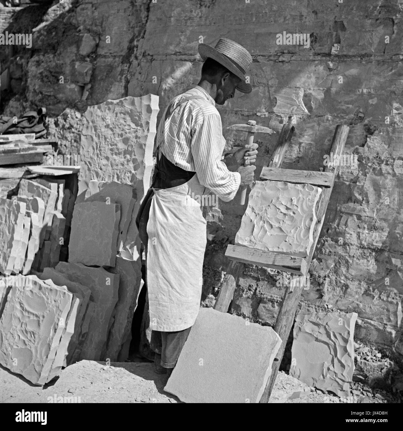 Stonemason working on slab in lithographic limestone quarry. - Stock Image
