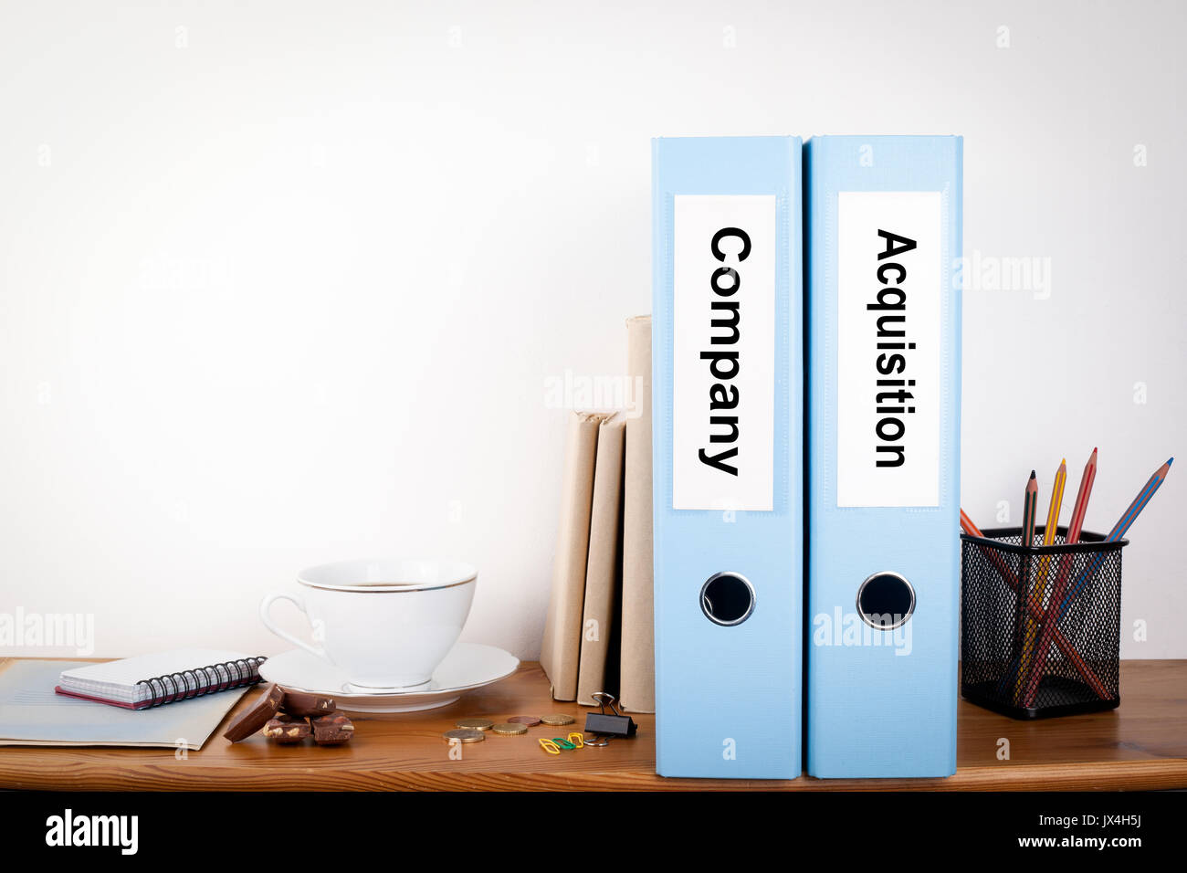 Company and Acquisition binders in the office. Stationery on a wooden shelf. - Stock Image