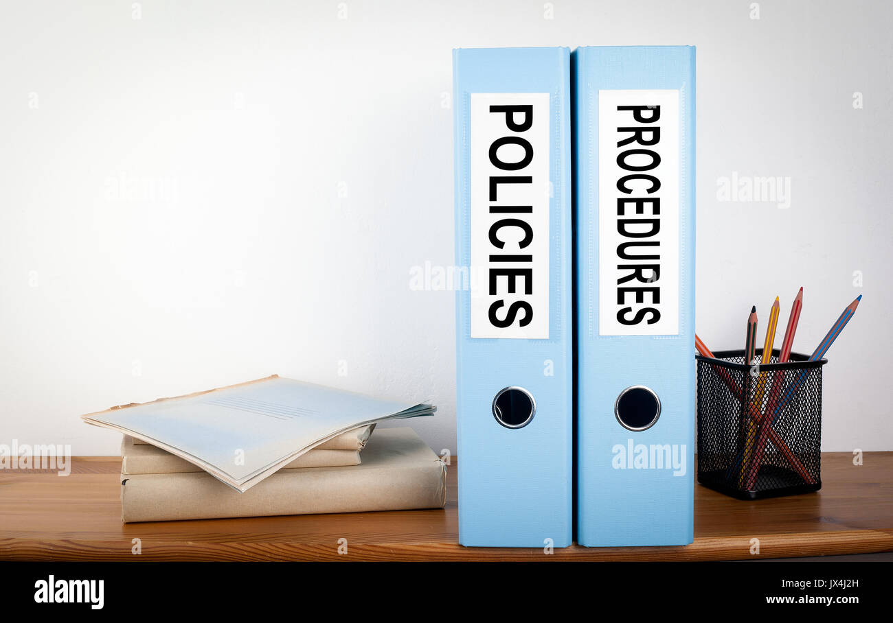 Policies and Procedures binders in the office. Stationery on a wooden shelf. - Stock Image