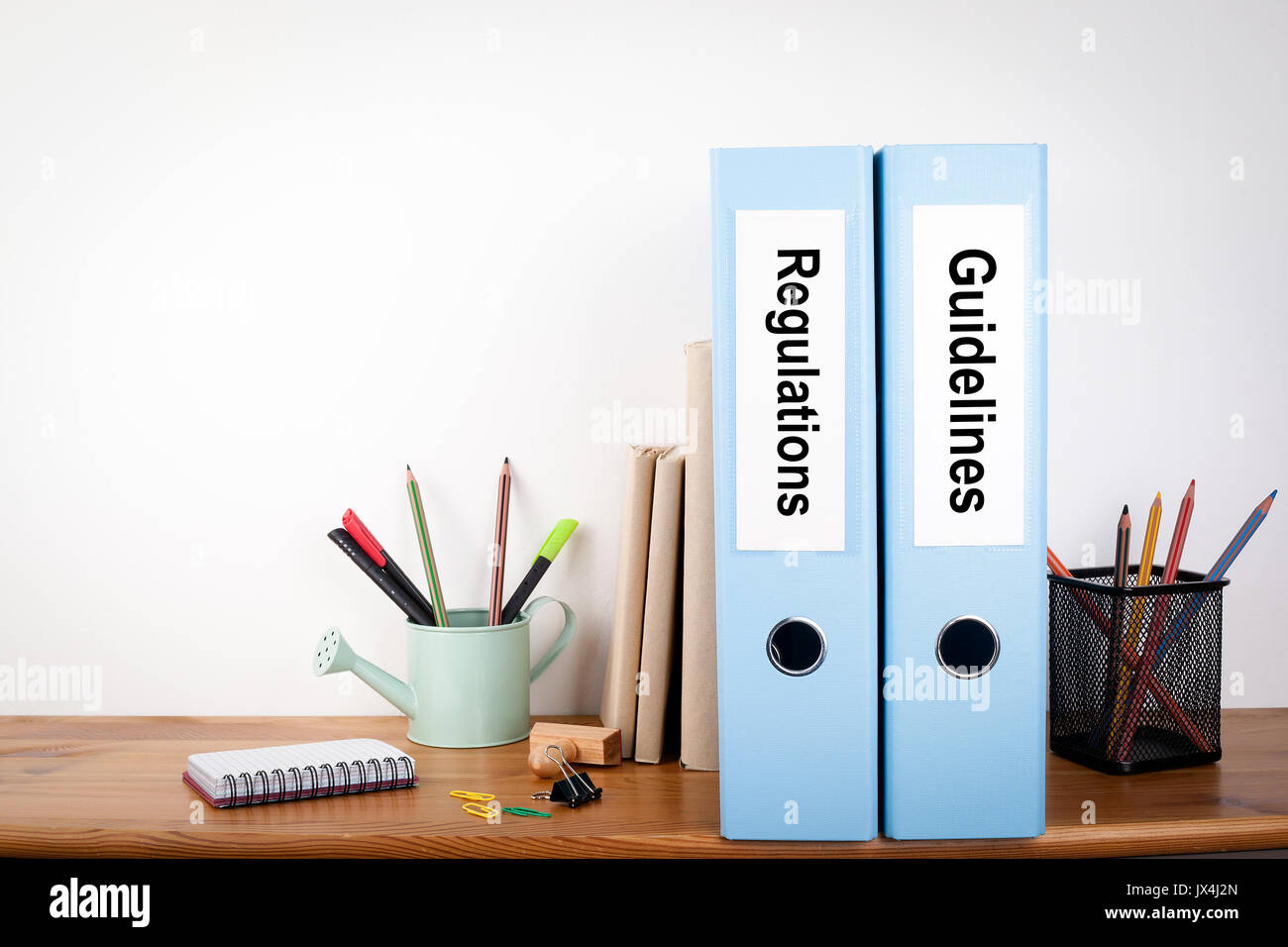 Regulations and Guidelines binders in the office. Stationery on a wooden shelf. - Stock Image