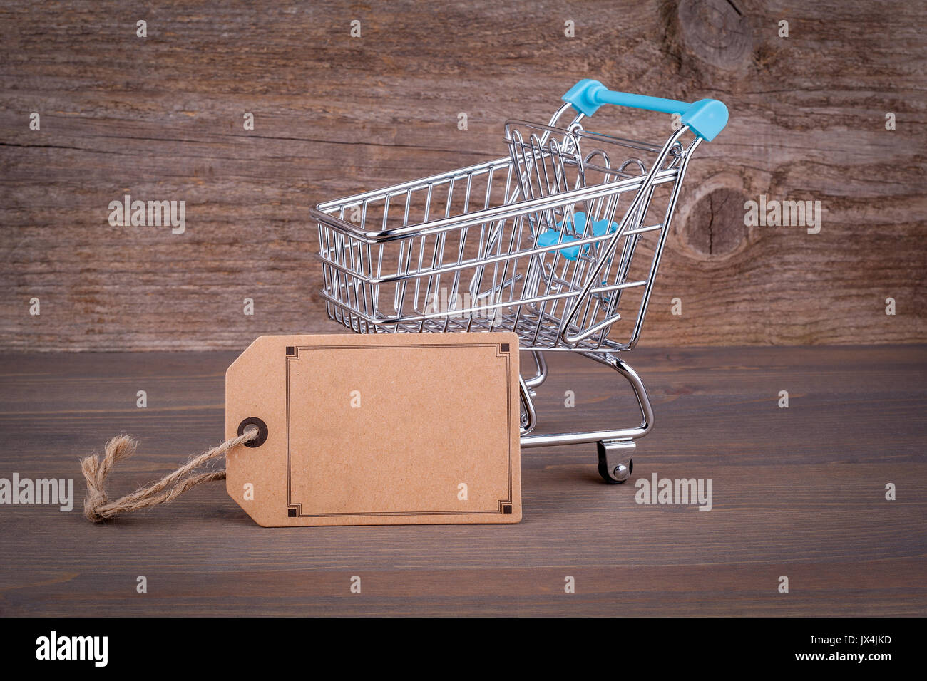 Purchasing cart with a blank price tag on a dark wooden background. - Stock Image