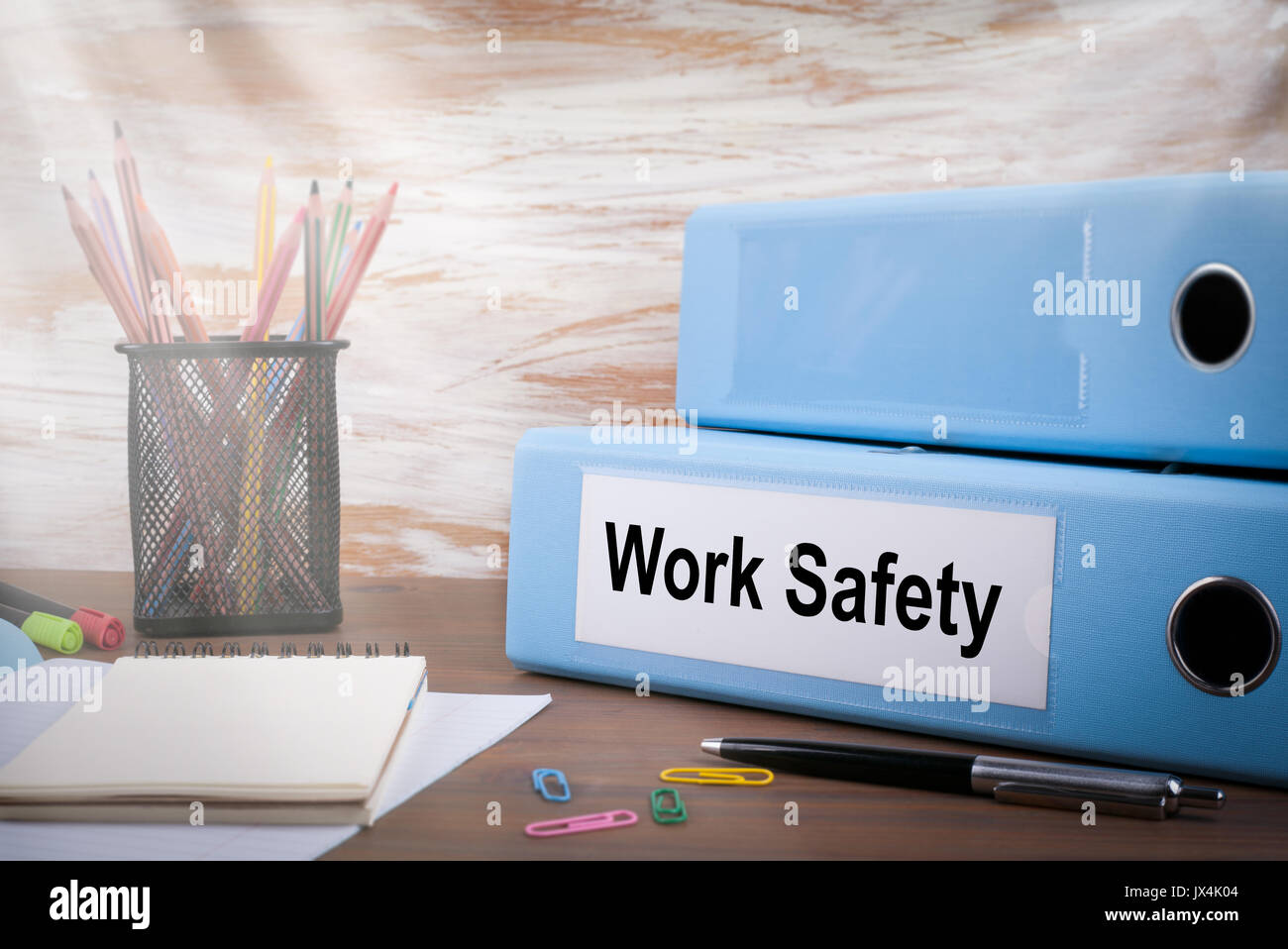 Work Safety, Office Binder on Wooden Desk. On the table colored pencils, pen, notebook paper. - Stock Image