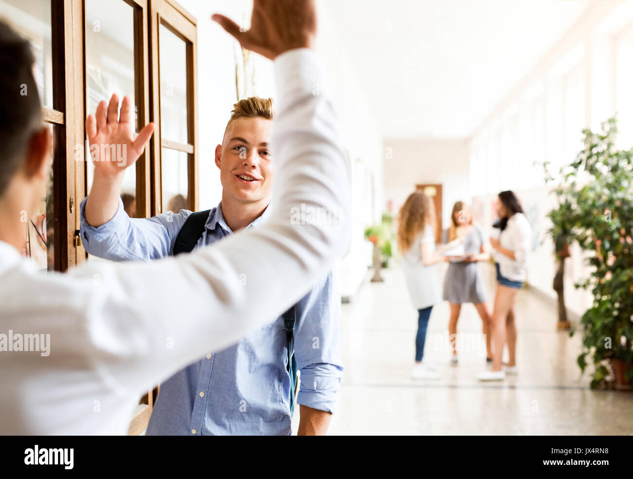 Two handsome teenage students in high school hall giving high five. - Stock Image
