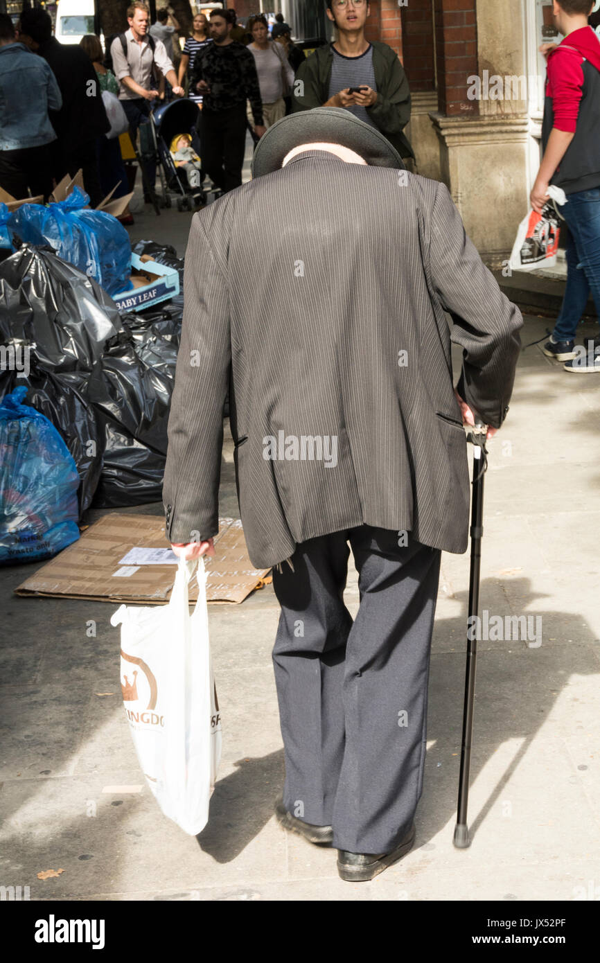 A hunched-up old man, with a walking stick and carrier bag, walking in London - Stock Image