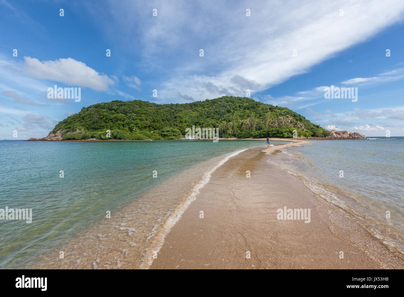 Lone young woman crossing tidal sandbar connecting Ko Ma island to Mae Haad beach, Koh Phangan island, Thailand - Stock Image