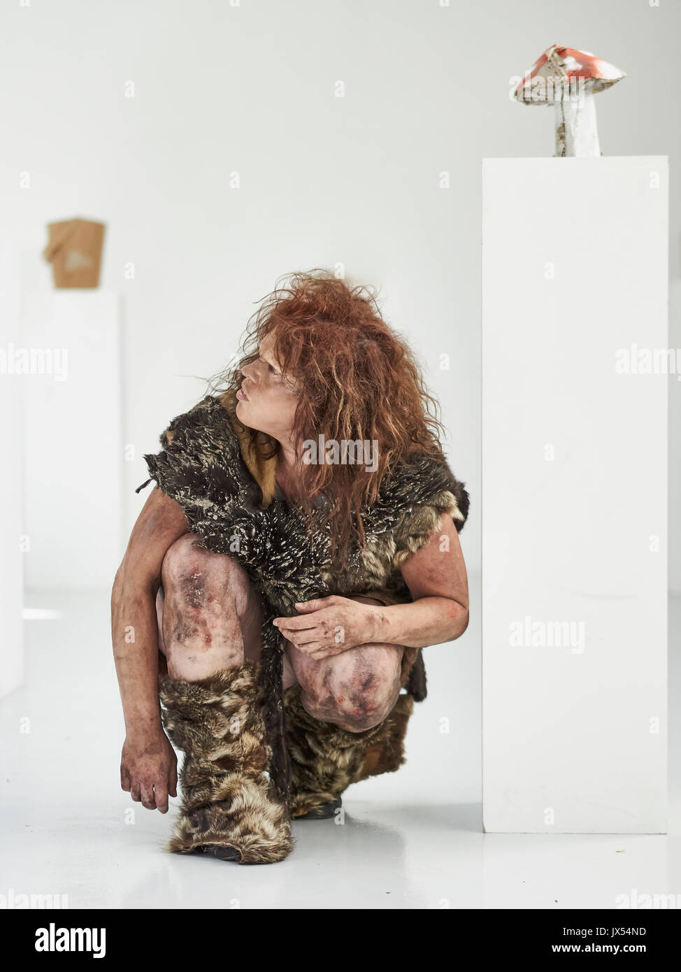 A primative prehistoric cave woman in an art gallery - Stock Image