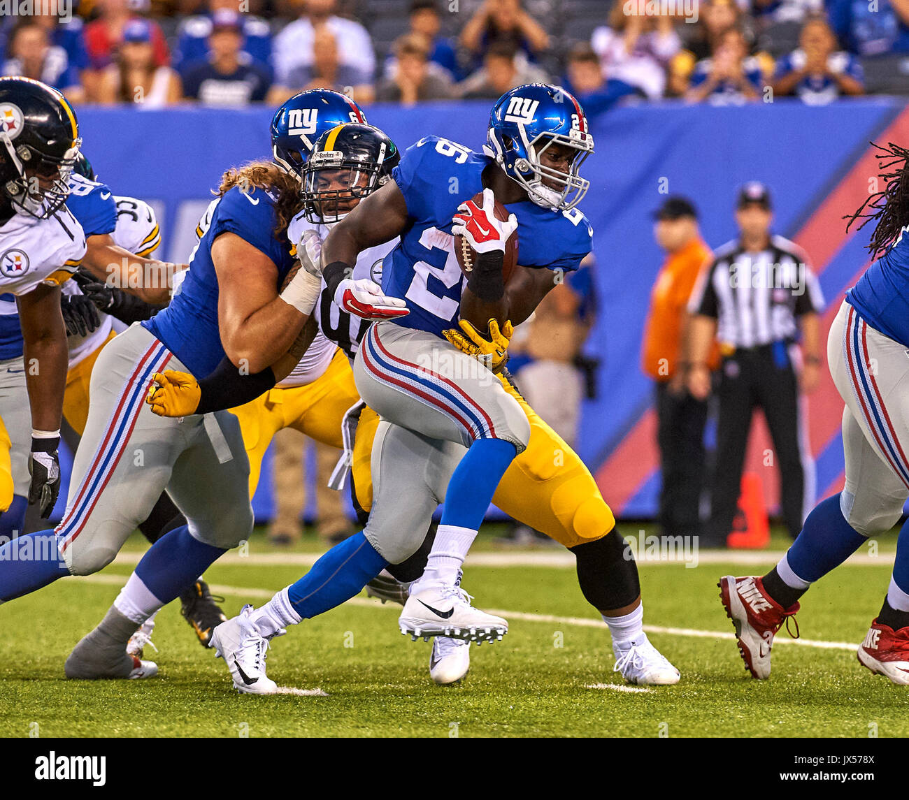 August 11, 2017 - East Rutherford, New Jersey, U.S. - Giants' running back Orleans Darkwa (26) tries to find running room around Steelers' defensive end Tyson Alualu (94) during NFL pre-season action between the Pittsburgh Steelers and the New York Giants at MetLife Stadium in East Rutherford, New Jersey. Duncan Williams/CSM - Stock Image