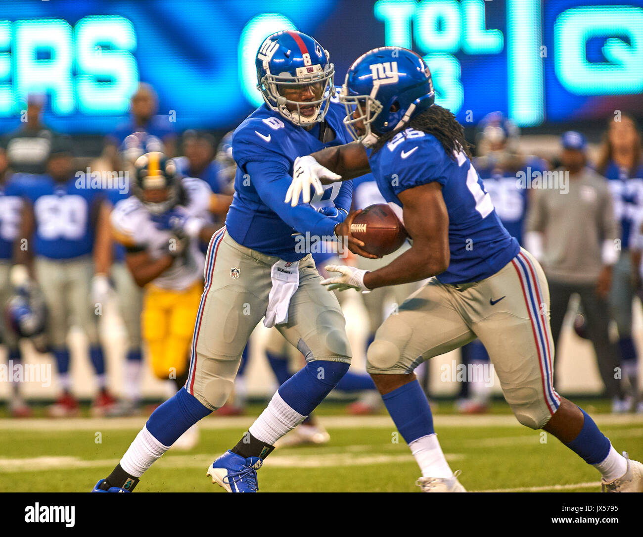 August 11, 2017 - East Rutherford, New Jersey, U.S. - Giants' quarterback Josh Johnson (8) hands off to running back Orleans Darkwa (26) during NFL pre-season action between the Pittsburgh Steelers and the New York Giants at MetLife Stadium in East Rutherford, New Jersey. Duncan Williams/CSM - Stock Image