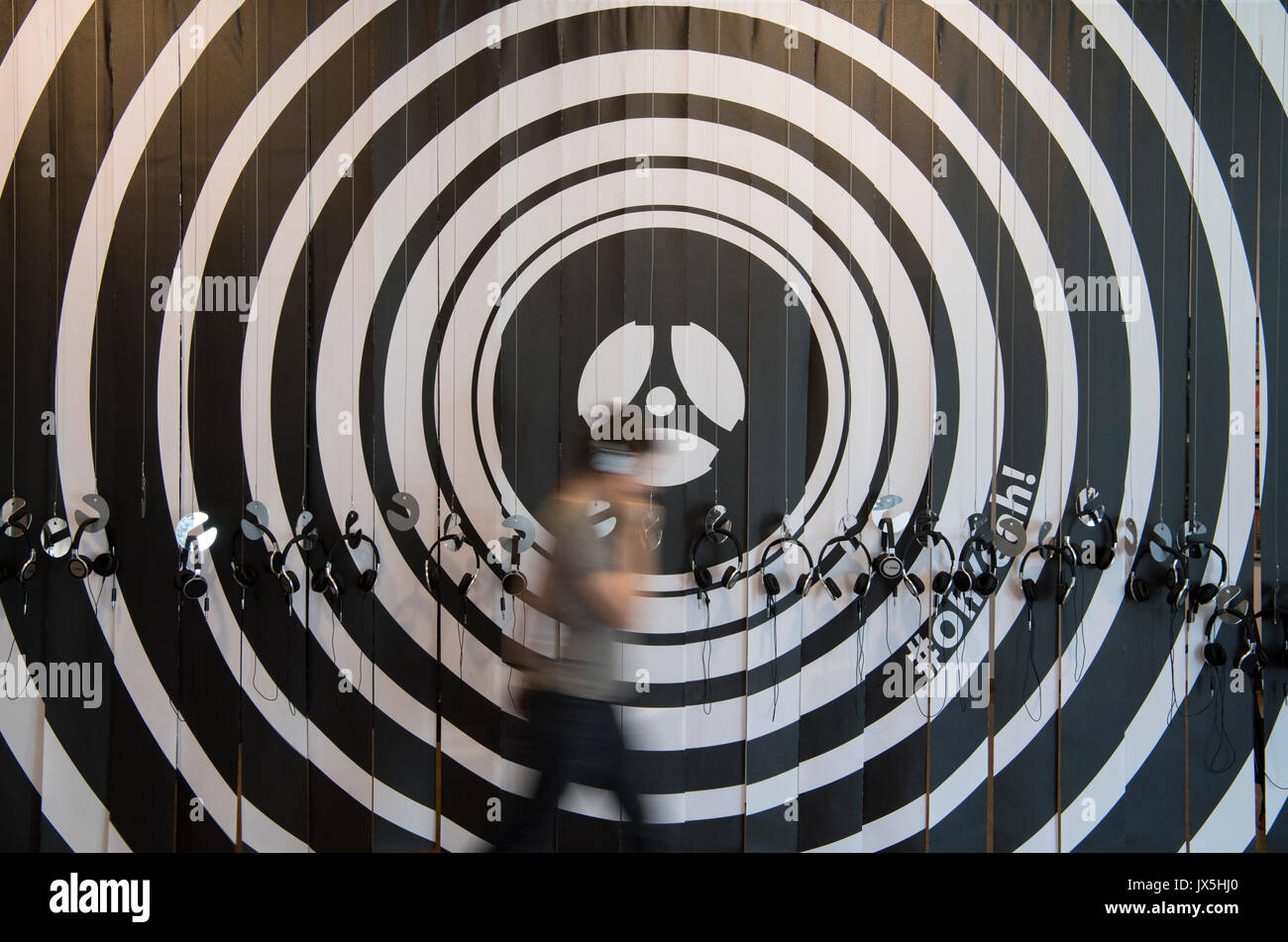 Headphones for visitors hanging in front of a stylised record during the press tour of the temporary exhibition ·Oh Yeah! Pop music in Germany·. in the Communications Museum in Frankfurt am Main, Germany, 15 August 2017. Photo: Boris Roessler/dpa - Stock Image