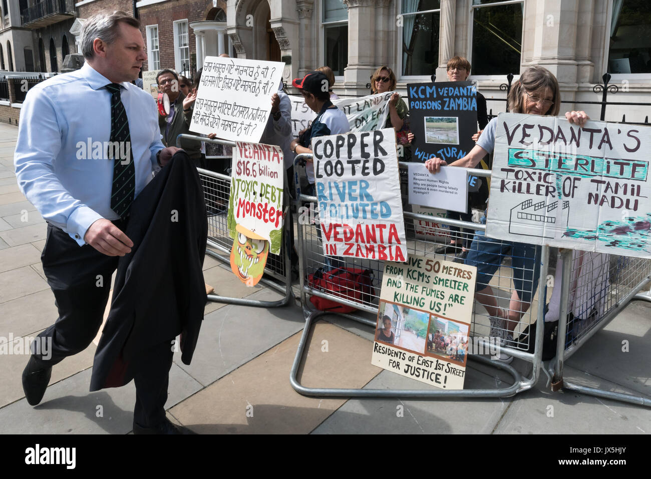 London, UK. 14th Aug, 2017. London, UK. 14th August 2017. A man attending the Vedanta AGM walks past the noisy protest by grass roots campaign Foil Vedanta. The protesters accuse Vedanta of illegal mining in Goa, of increasing harassment, torture and false accusations against tribal activists in Nyamgiri, Odisha, who have used Indian laws to stop bauxite mining of their sacred mountain, eleven years of ruinous and continuing pollution by Konkola Copper Mines (KCM) in Zambia, where they say the company have fraudulently avoided taxes and failed to publish mandatory accounts and other offen - Stock Image