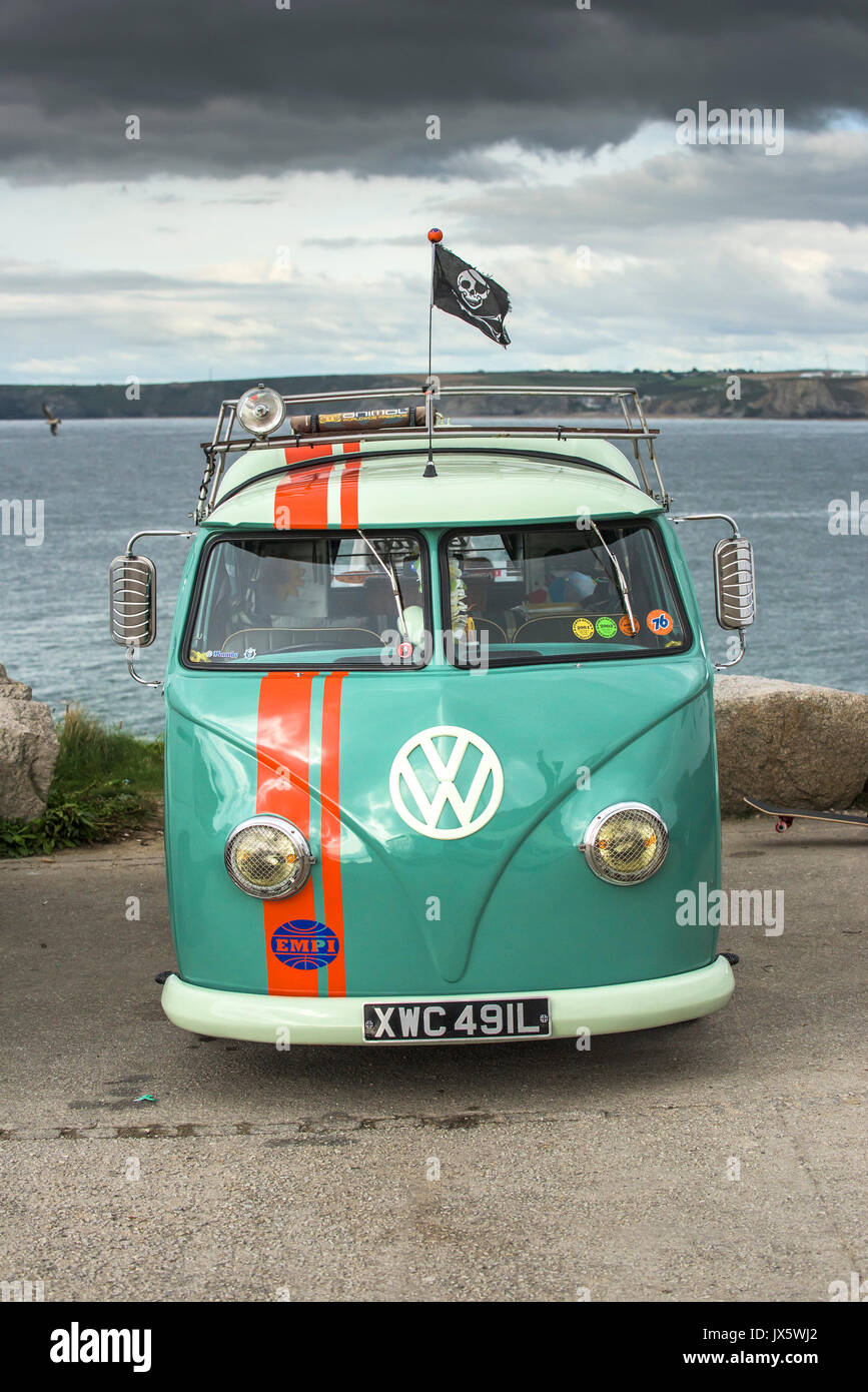 A vintage VW campervan parked on the coast of Cornwall. - Stock Image