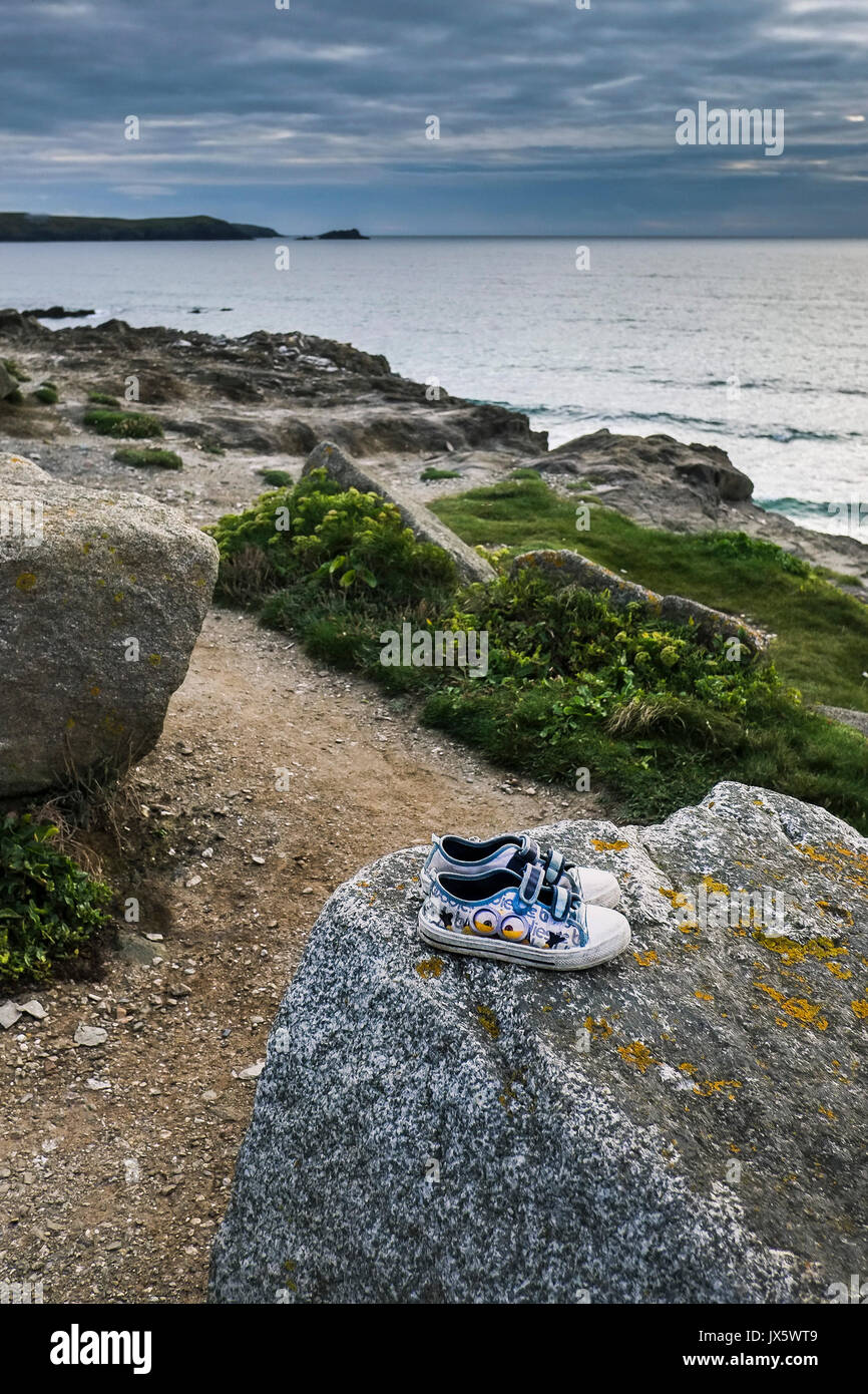 A pair of childrens trainers left behind on a rock at Little Fistral in Newquay, Cornwall. - Stock Image