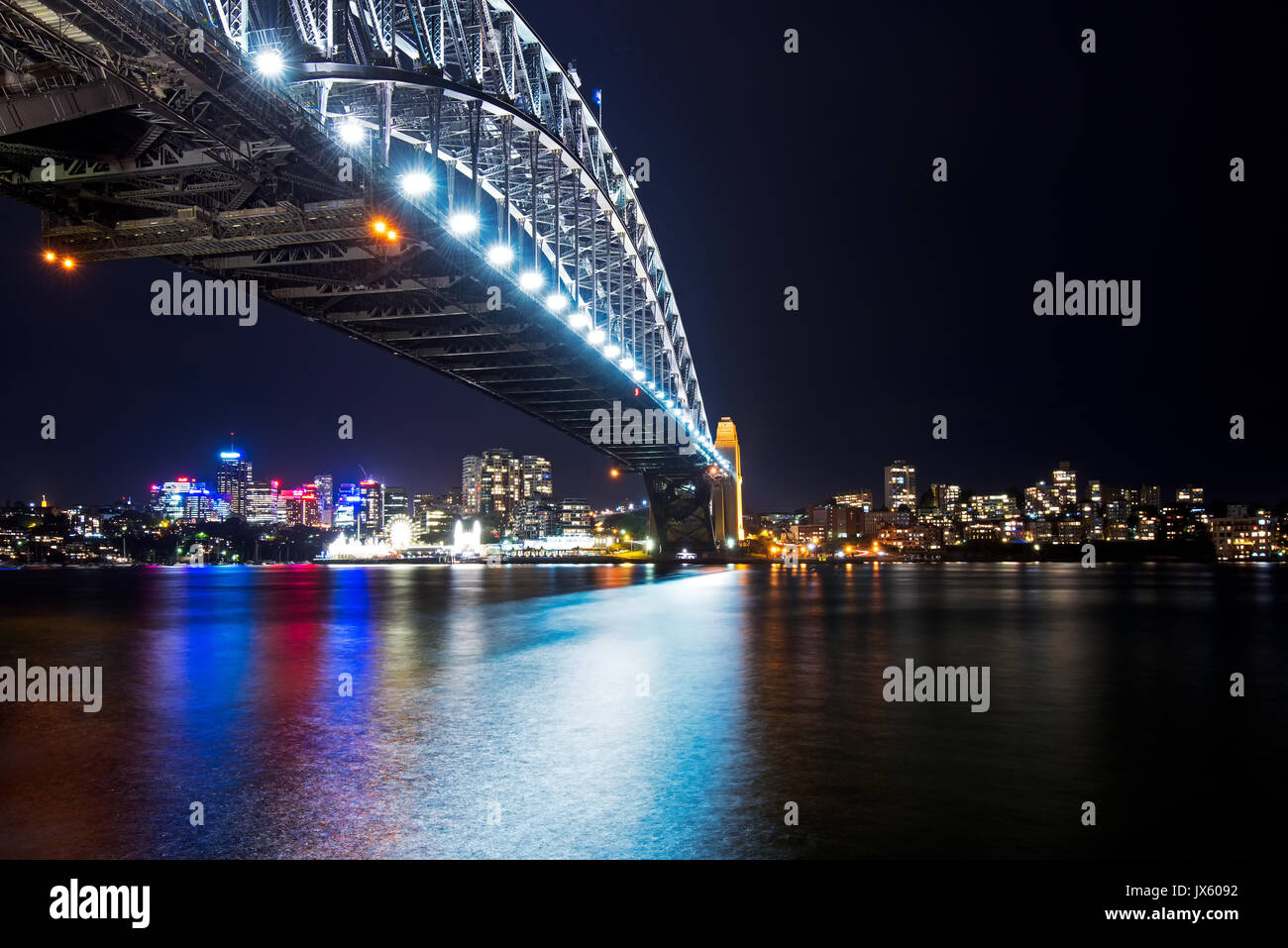 Colorful light reflection at Sydney Harbour Bridge at Night from Circular Quay, Sydney, Australia - Stock Image