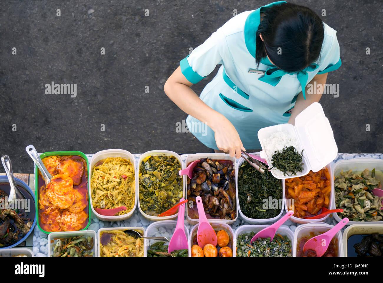 Kota Kinabalu, Malaysia - August 1, 2017: Directly above shot of a woman choosing a food at the self service street food stall in Kota Kinabalu, Sabah - Stock Image