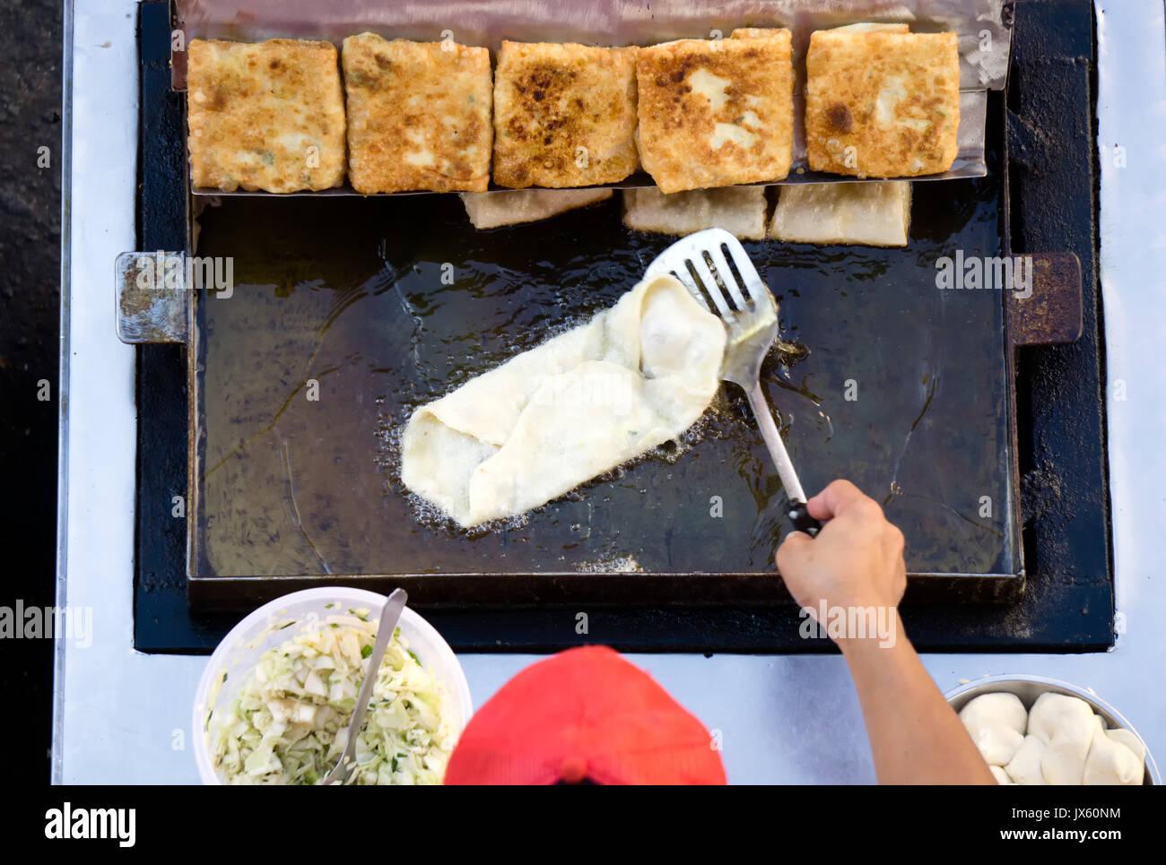 Top view of a man hand cooking vegetables martabak jawa in Kota Kinabalu City open market in Sabah Borneo. Martabak Jawa also known as stuffed pancake - Stock Image