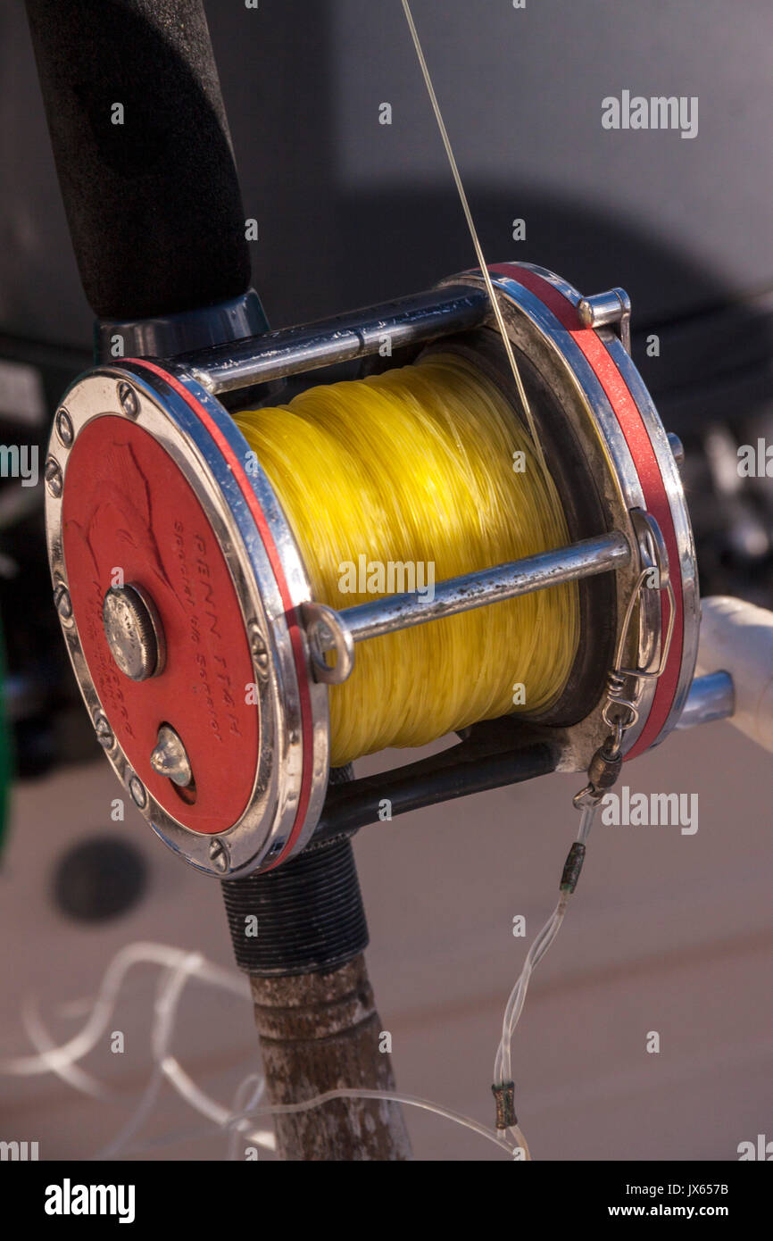 A large sea fishing reel with yellow line aboard a speed boat in Barbados, Caribbean Isles - Stock Image