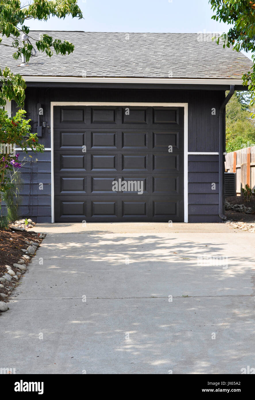 Charmant Exterior Single Car Garage With The Door Closed In A Dark Gray Or Charcoal  Color At The End Of A Driveway.