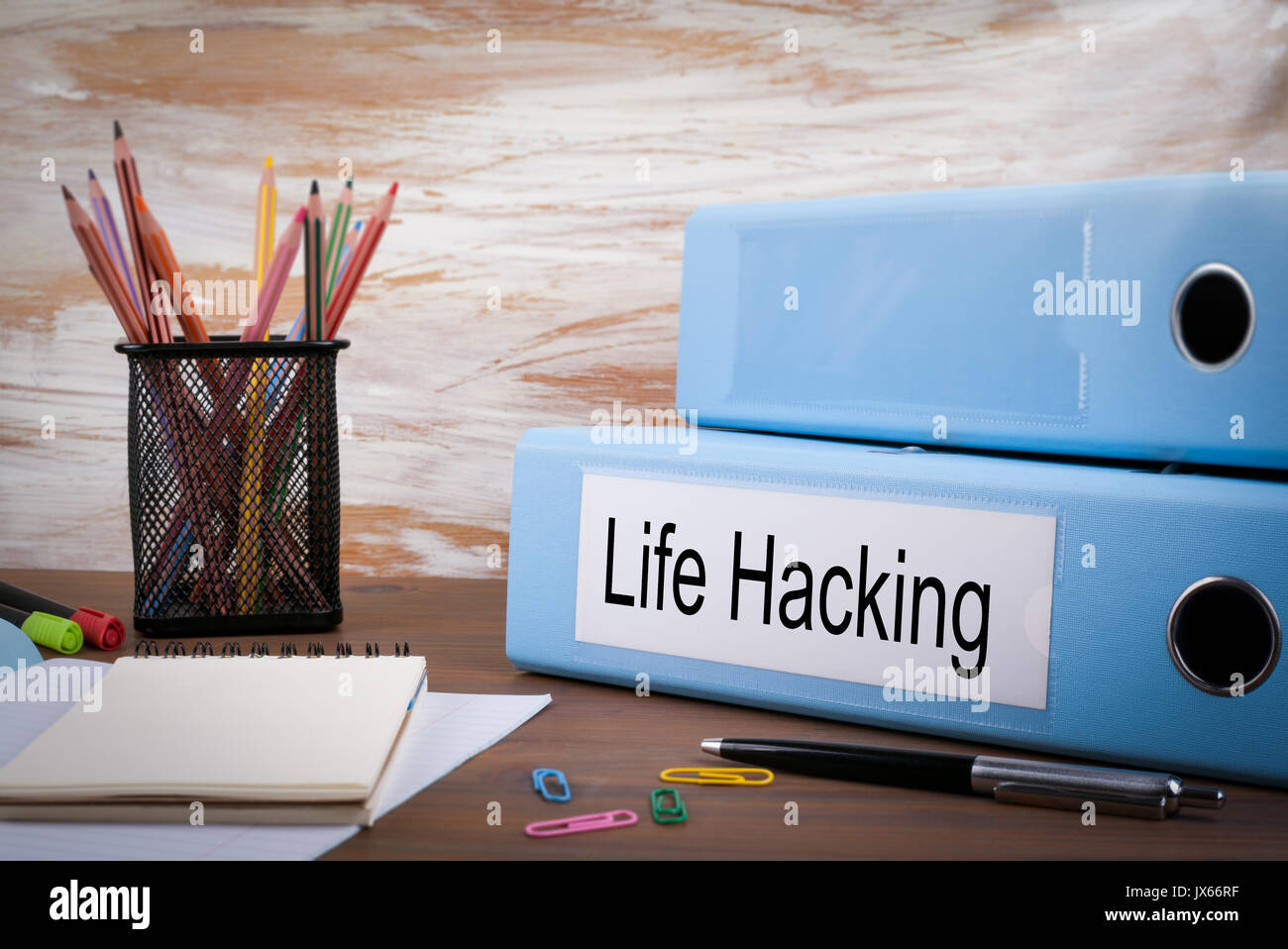 Life Hacking, Office Binder on Wooden Desk. On the table colored pencils, pen, notebook paper. - Stock Image