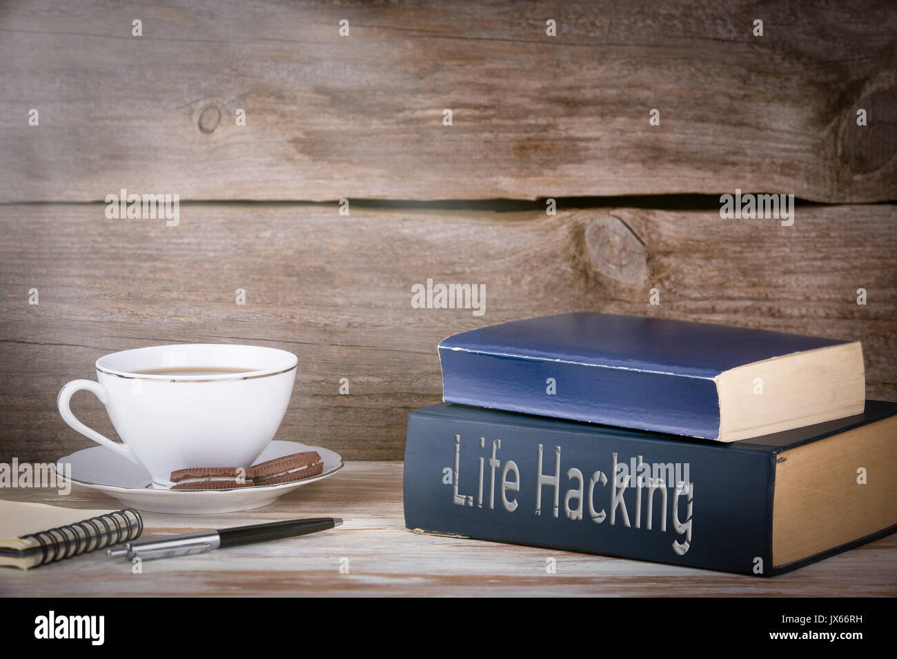 Life Hacking. Stack of books on wooden desk. - Stock Image