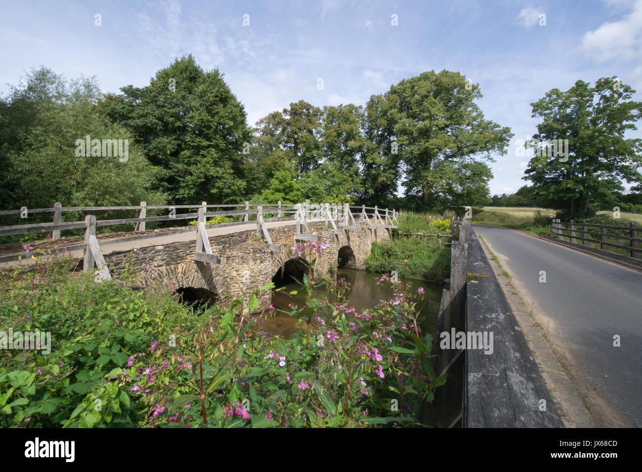 Medieval bridge over the River Wey at Tilford village in Surrey, UK - Stock Image