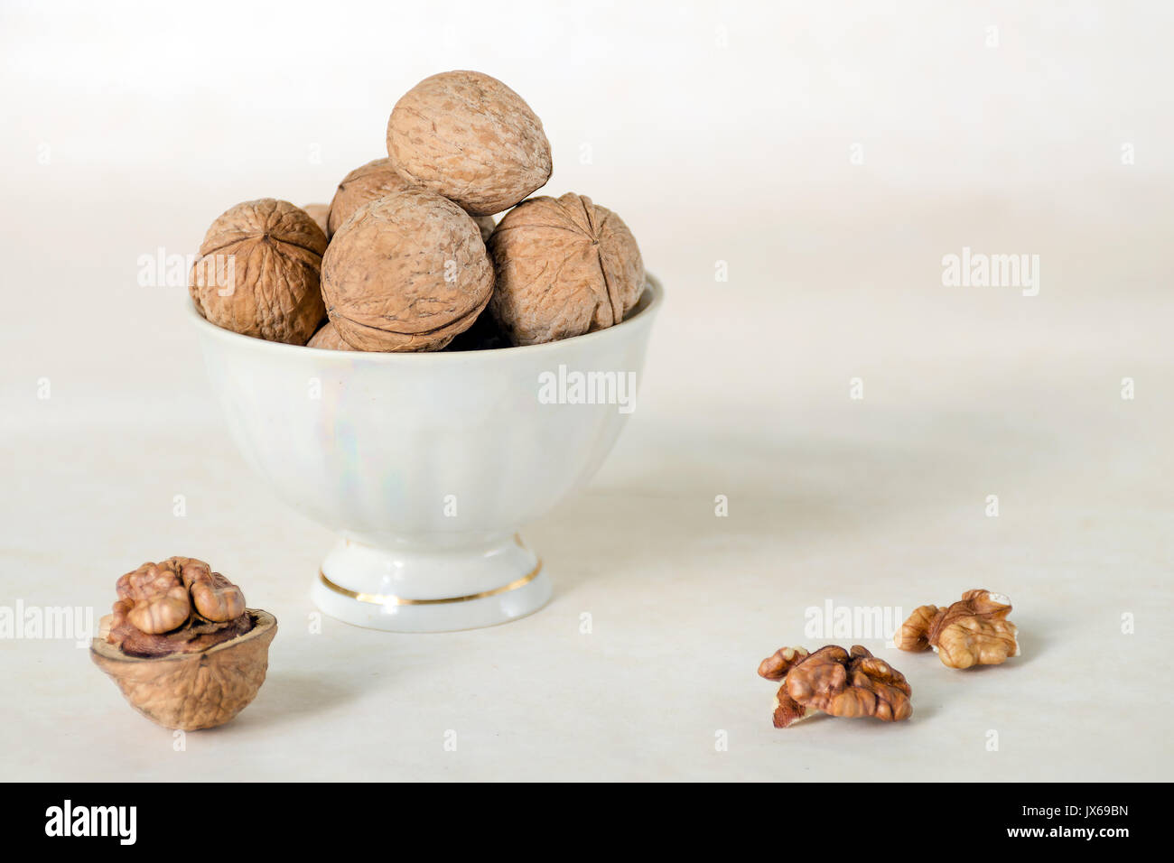 Walnut in a shell are stacked in a white cup. Next peeled nuts. Vegetable protein is an analogue of an animal. Light - Stock Image