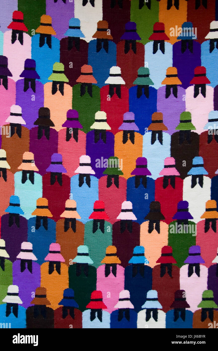 Colorful textile patterned texture of south american design featuring backs of women dressed in ponchos and hats. - Stock Image