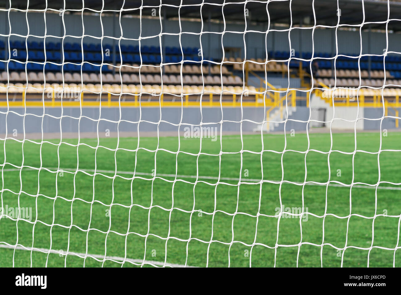 Behind goal of soccer field. Soccer football net background over green grass or soccer field and blurry empty stadium. Football,soccer field. Match wi - Stock Image