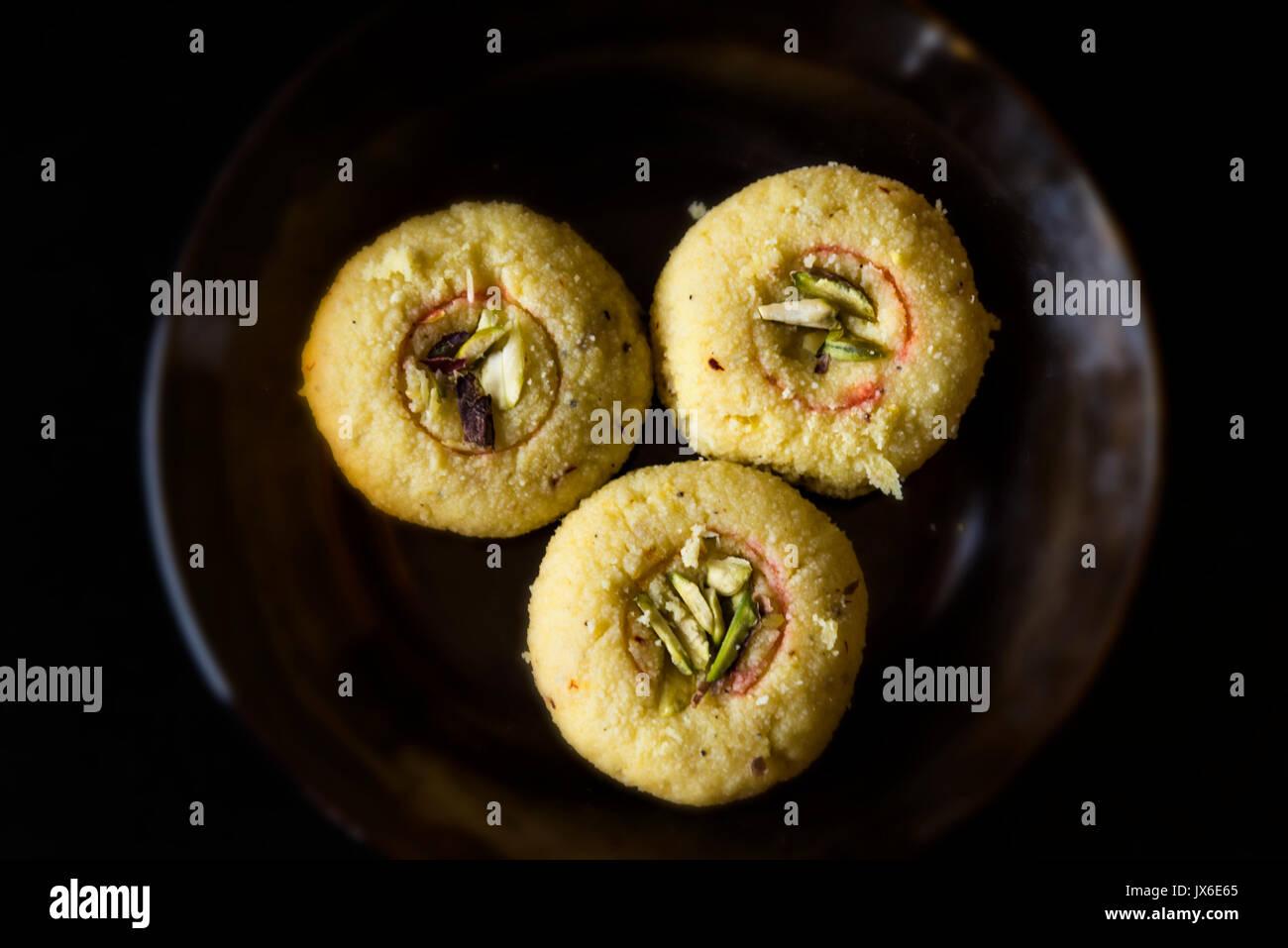 Indian Sweet, Kesar (Saffron) Peda with Garnishing of Pistachio and Cardamom - Stock Image