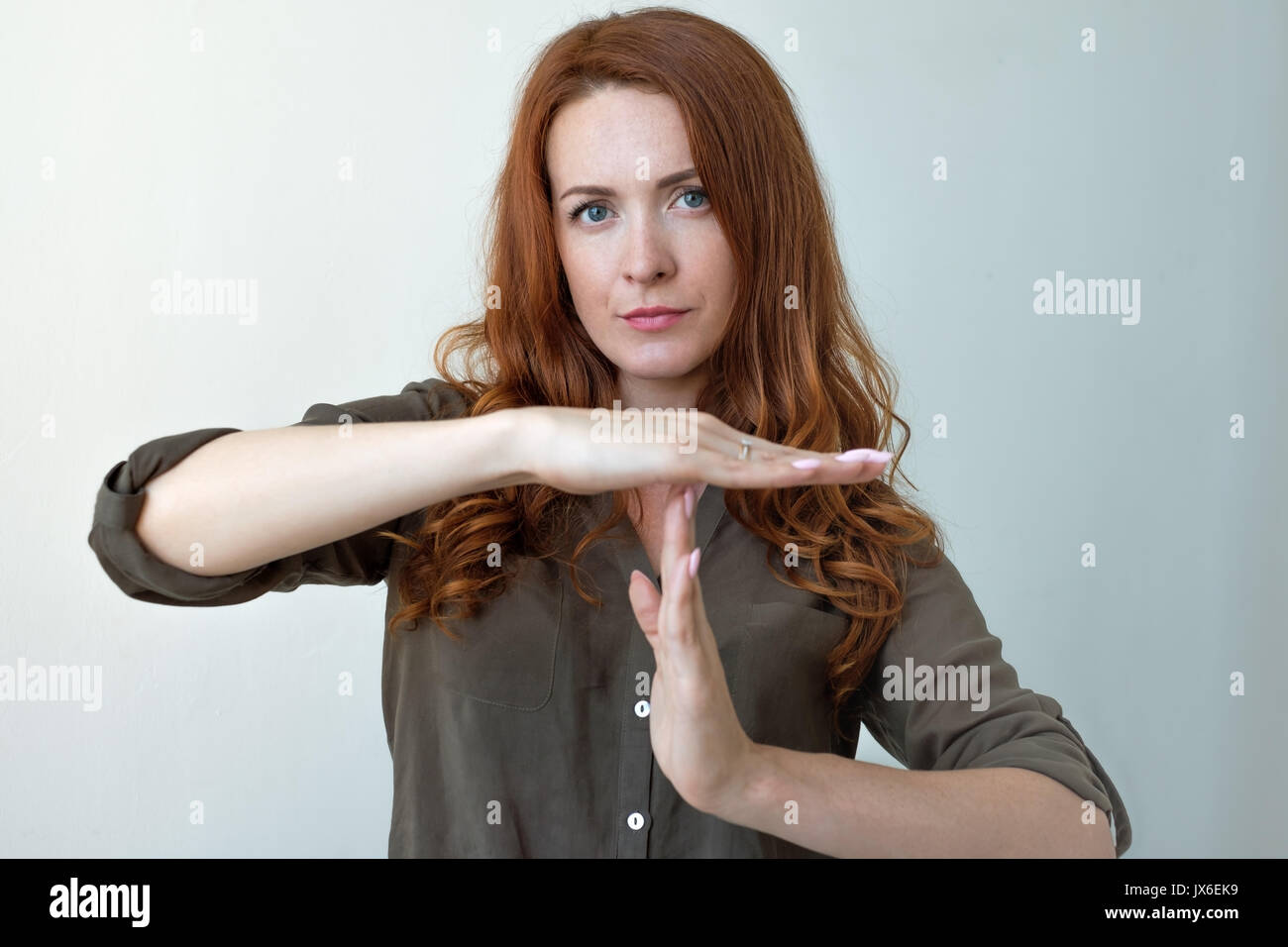 Young woman showing time out hand gesture, frustrated screaming to stop isolated on grey wall background. - Stock Image