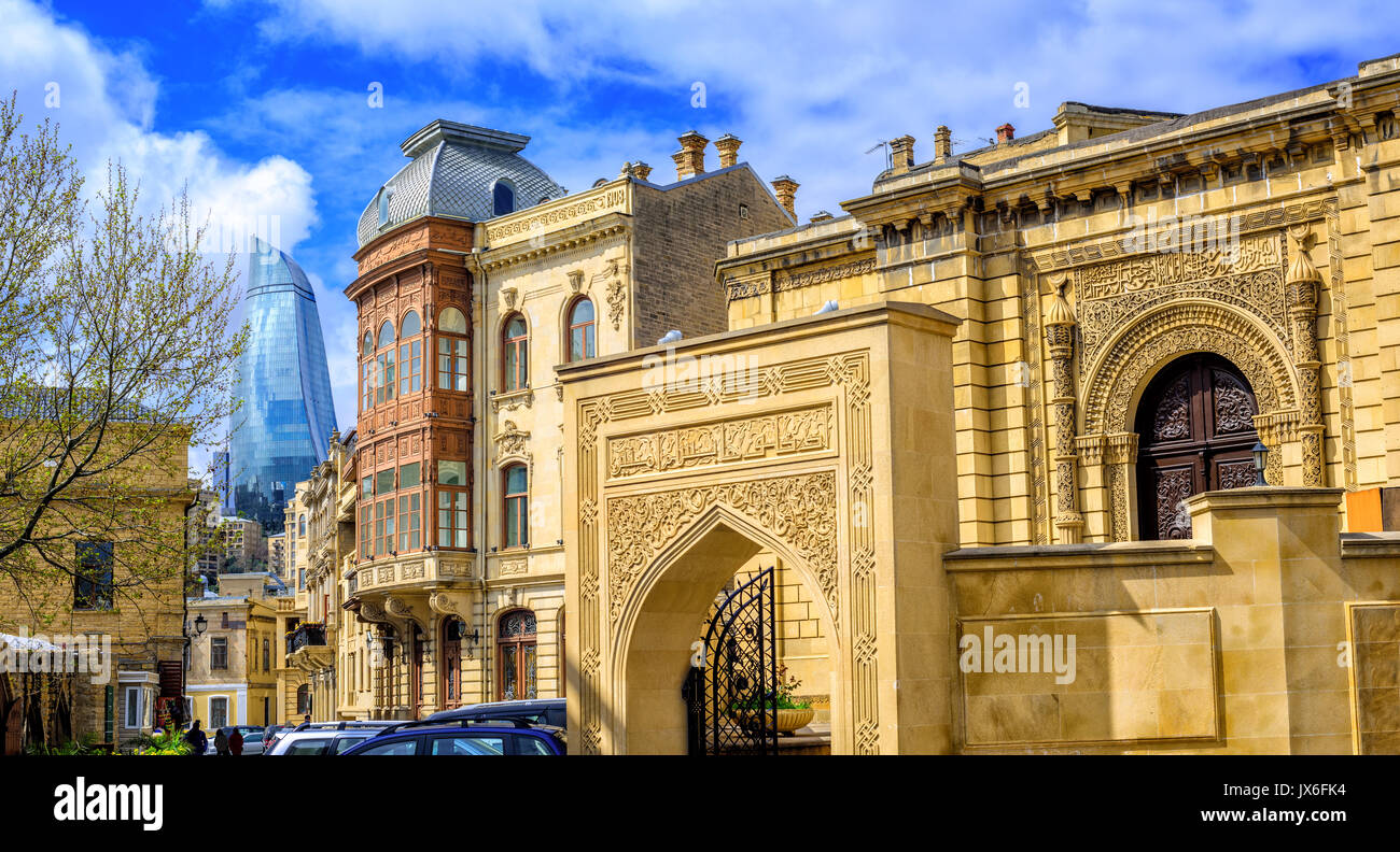 Panoramic view of Baku Old Town (Icheri Sheher), Azerbaijan, with modern glass Flame Tower skyscraper in background - Stock Image