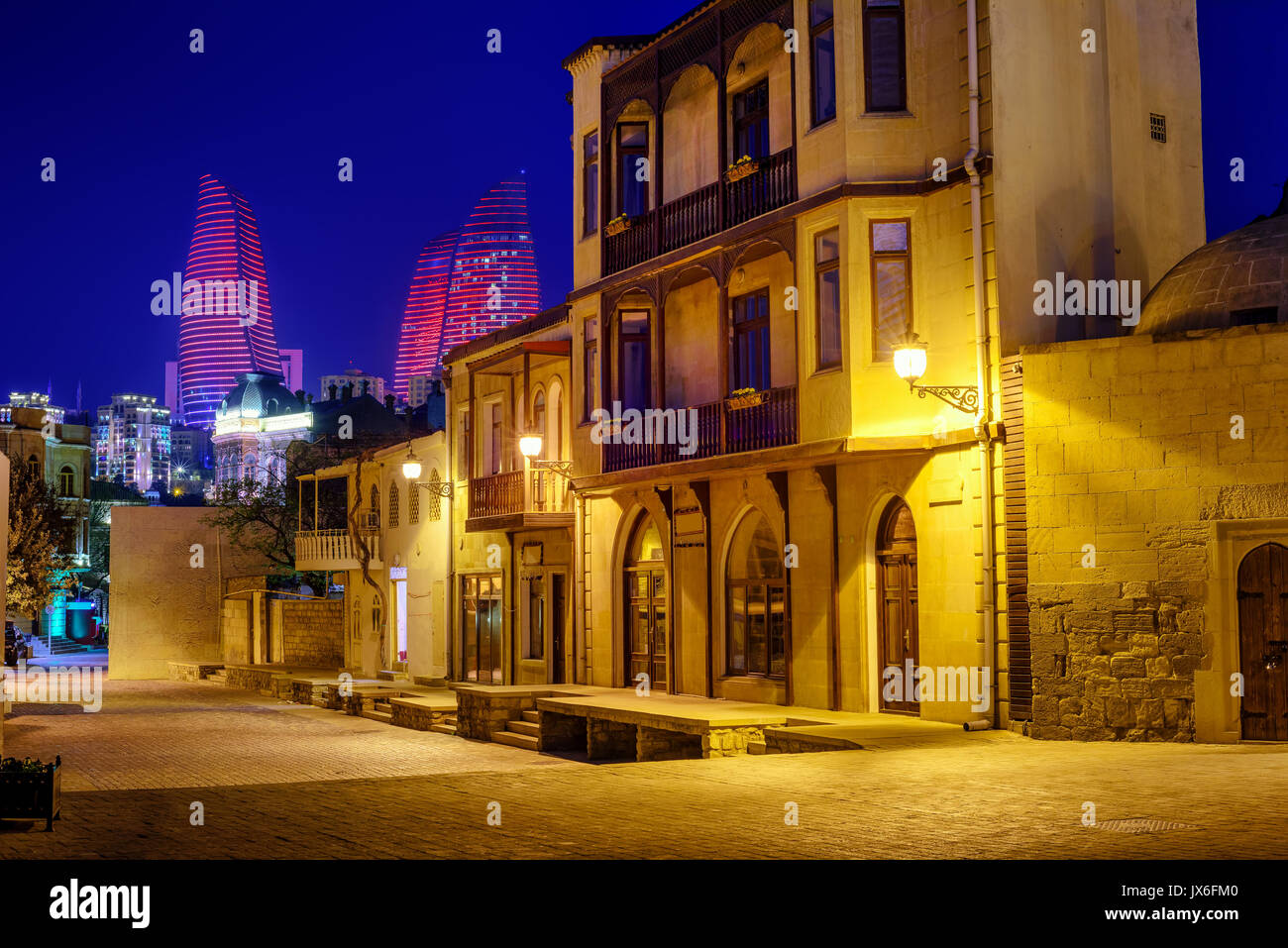 Historical houses in Baku Old Town and the illuminated Flame Towers at evening, Azerbaijan - Stock Image