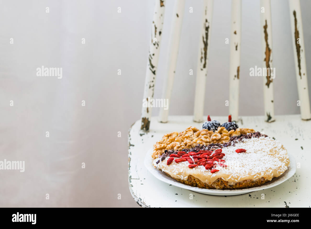 Raw vegan sweet carrot cake with cream topped with walnuts, goji berries, chocolate truffles, coconut flakes and cocoa crochet. Healthy homemade desse - Stock Image