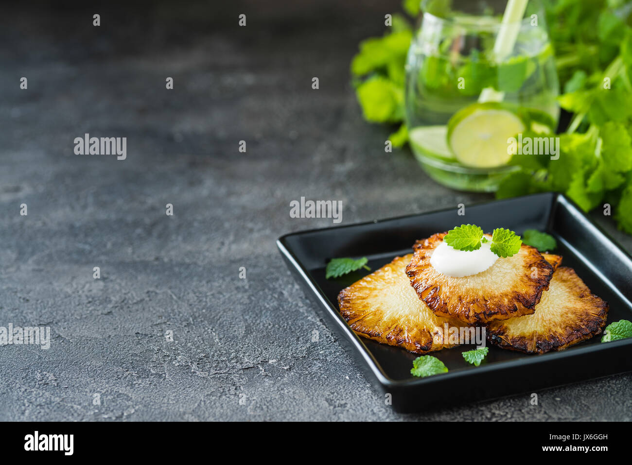 Fried pineapple slices with creme fraiche, mint on dark background. Copy space - Stock Image