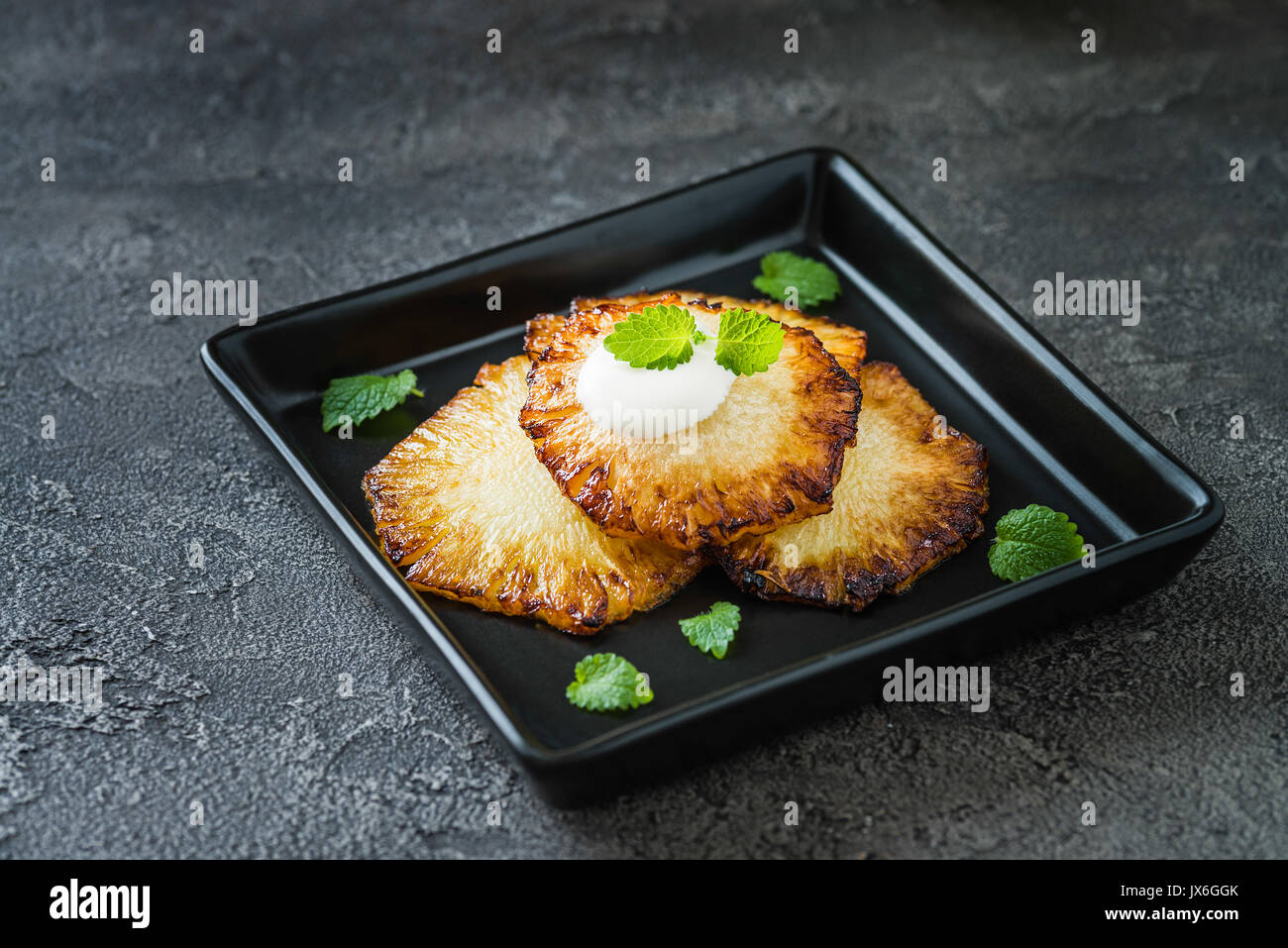Fried pineapple slices with creme fraiche, mint in black square plate on dark background - Stock Image