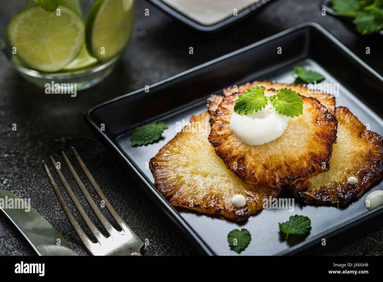 Fried pineapple slices with creme fraiche, mint in black square plate served with lime drink. Dark background - Stock Image