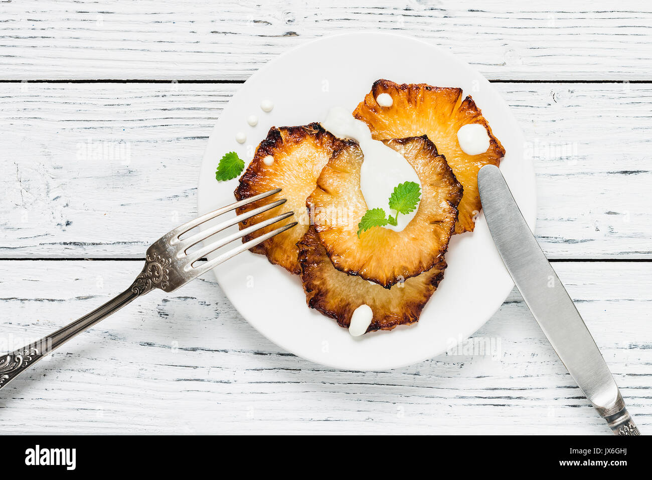 Fried pineapple slices with creme fraiche, mint in white plate on wooden background. Top view - Stock Image