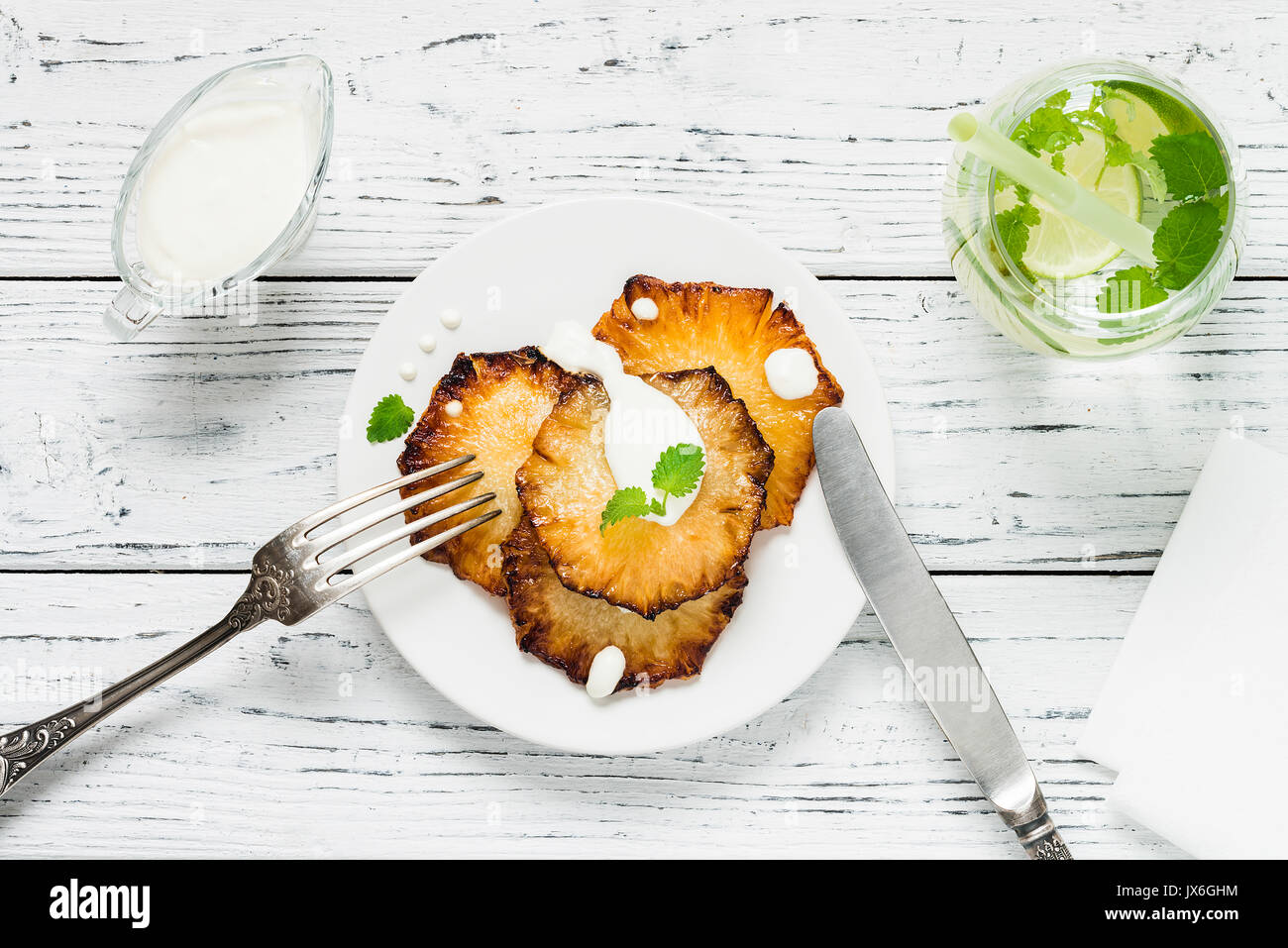 Fried pineapple slices with creme fraiche, mint in white plate served with lime drink on wooden background. Top view - Stock Image