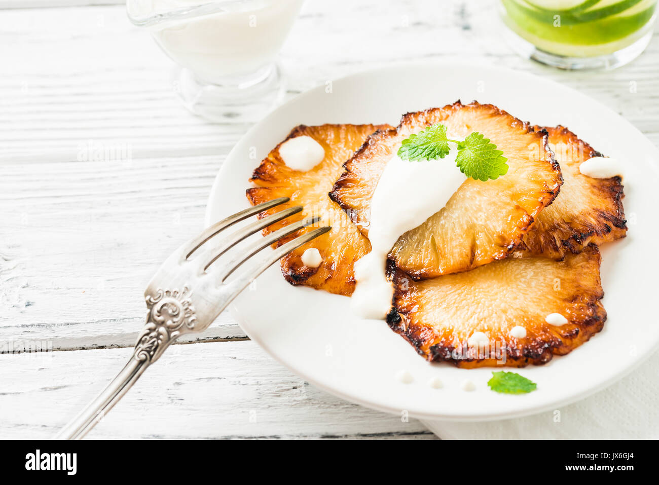 Fried pineapple slices with creme fraiche, mint in white plate on wooden background - Stock Image
