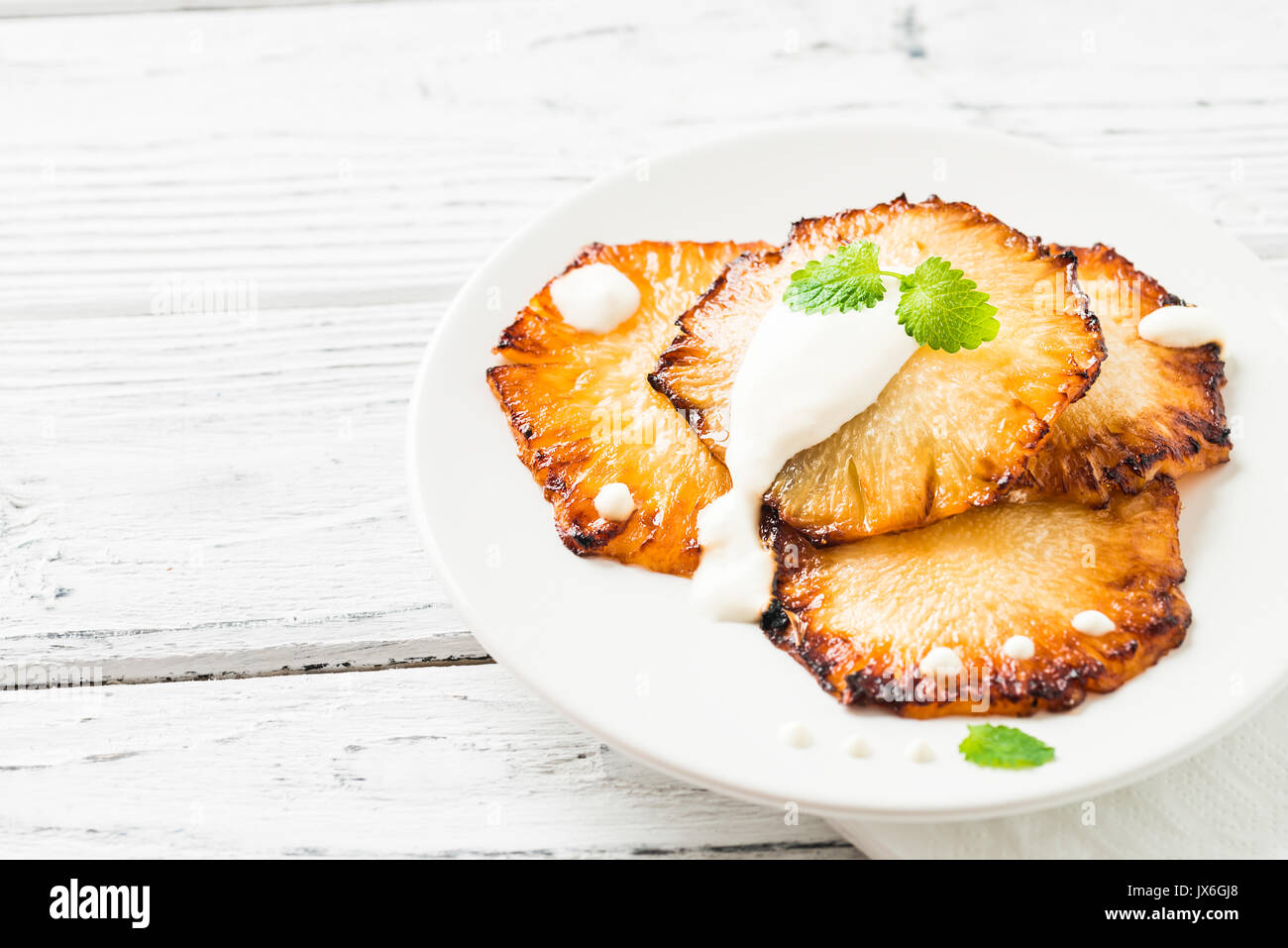 Fried pineapple slices with creme fraiche, mint in white plate on wooden background. Copy space - Stock Image